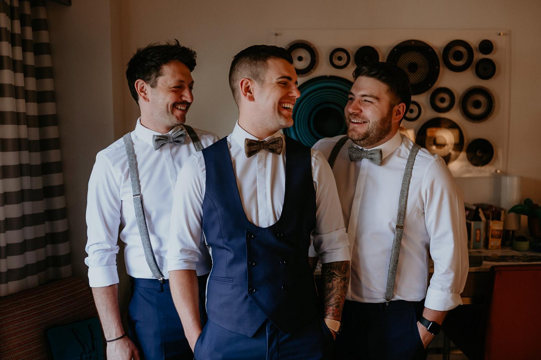 groomsmen inside hard rock hotel room laughing