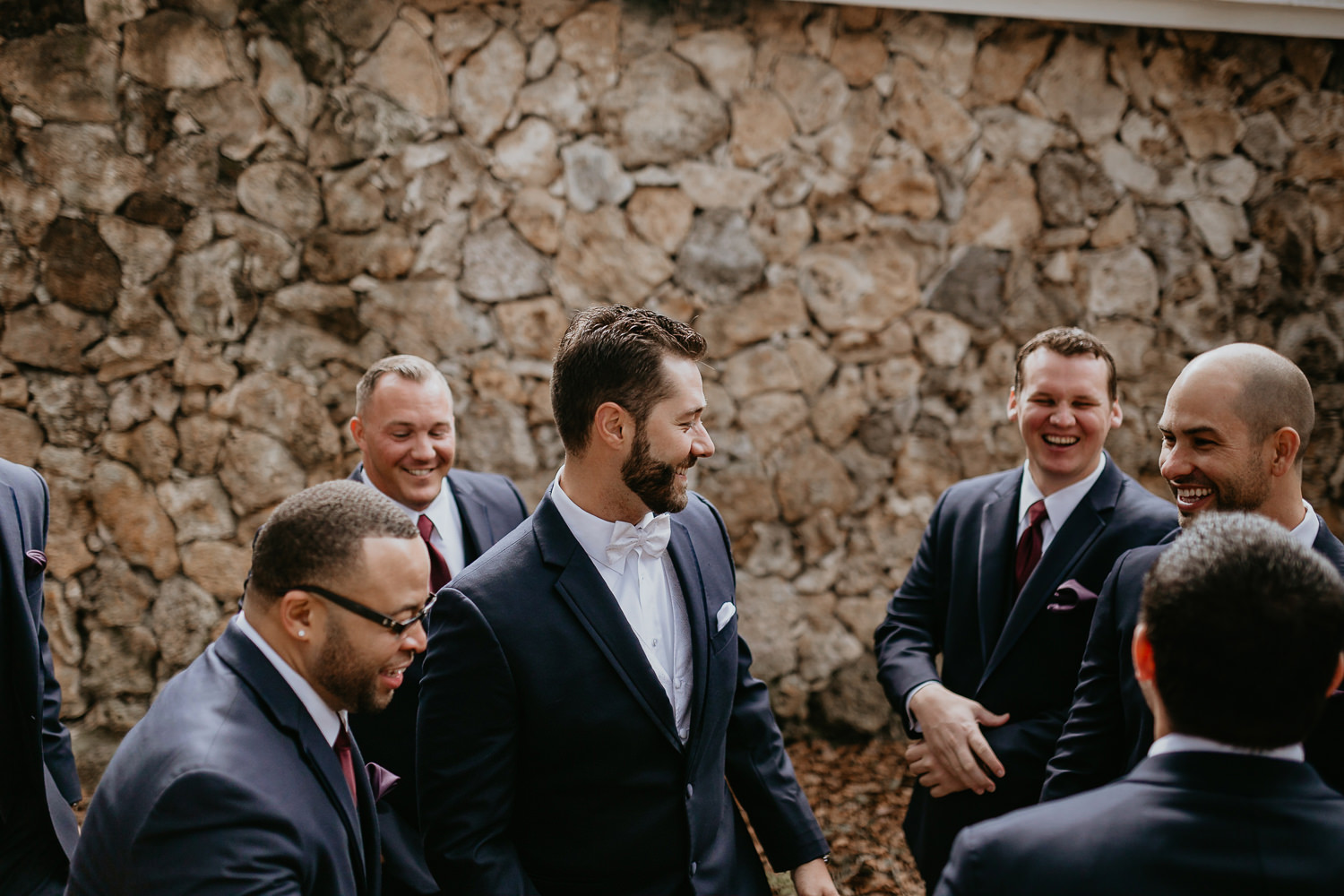 groomsmen huddled in front of stone wall with groom in the middle, all laughing