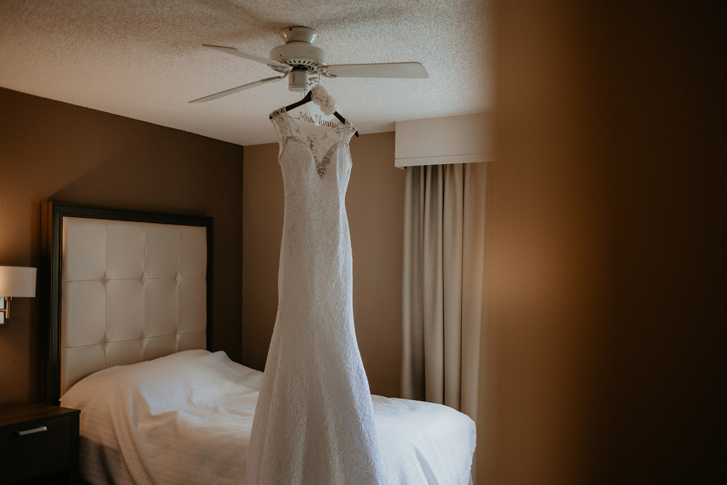 wedding dress hanging on fan inside hotel room