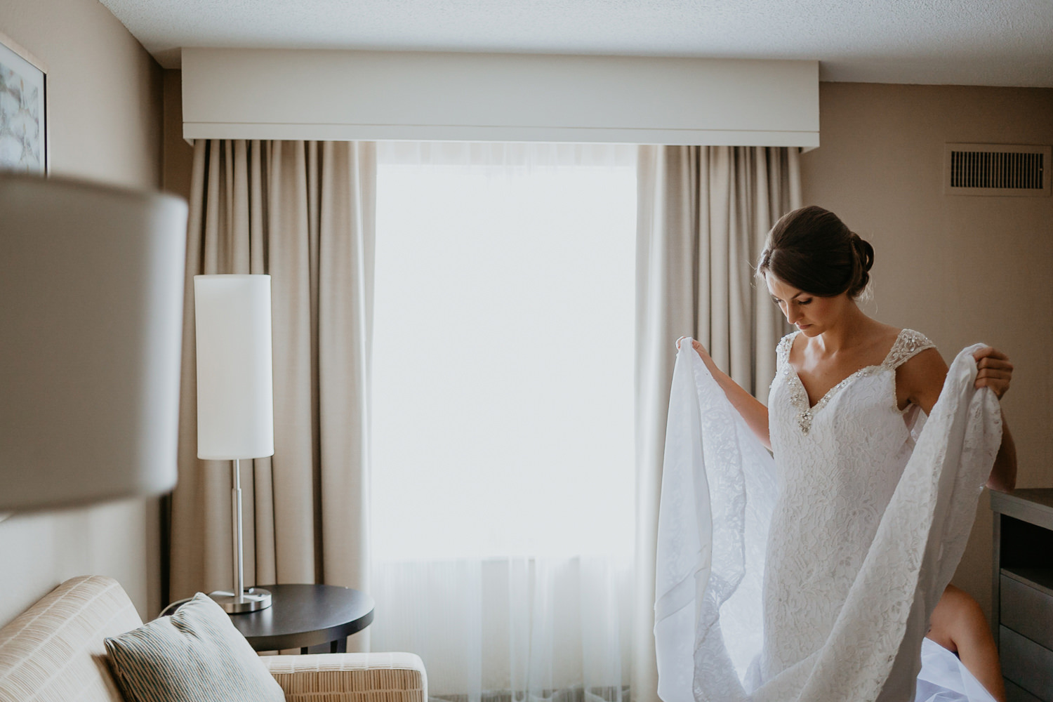 bride next to hotel window holding up her dress from the sides