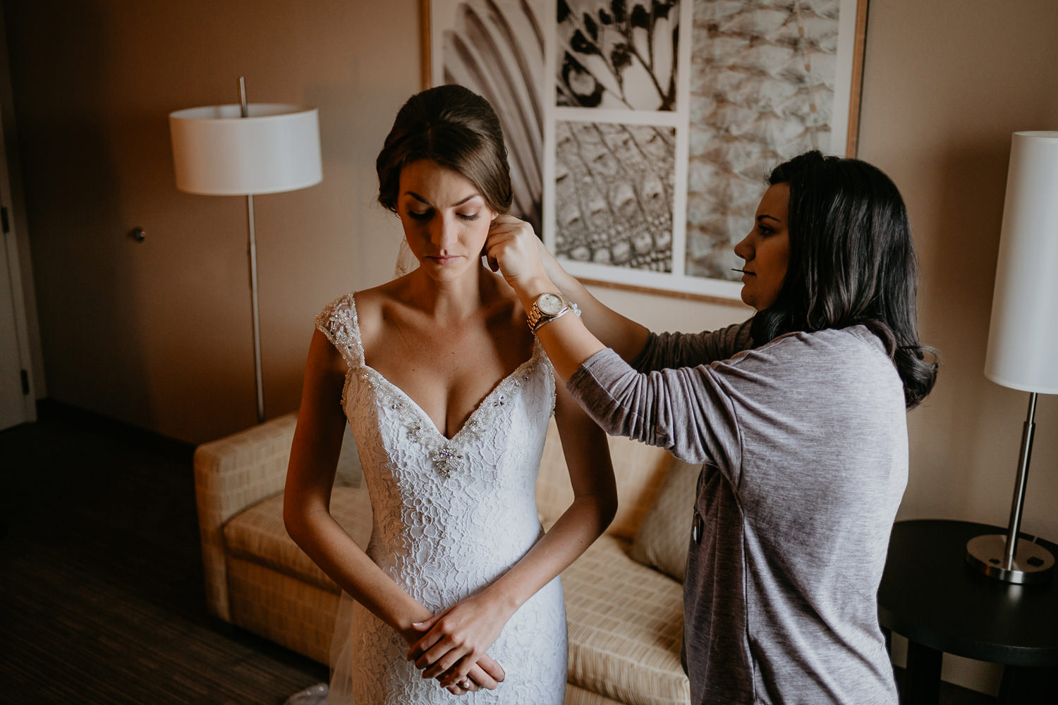 woman helping bride put on her earrings, bride looking down hands crossed