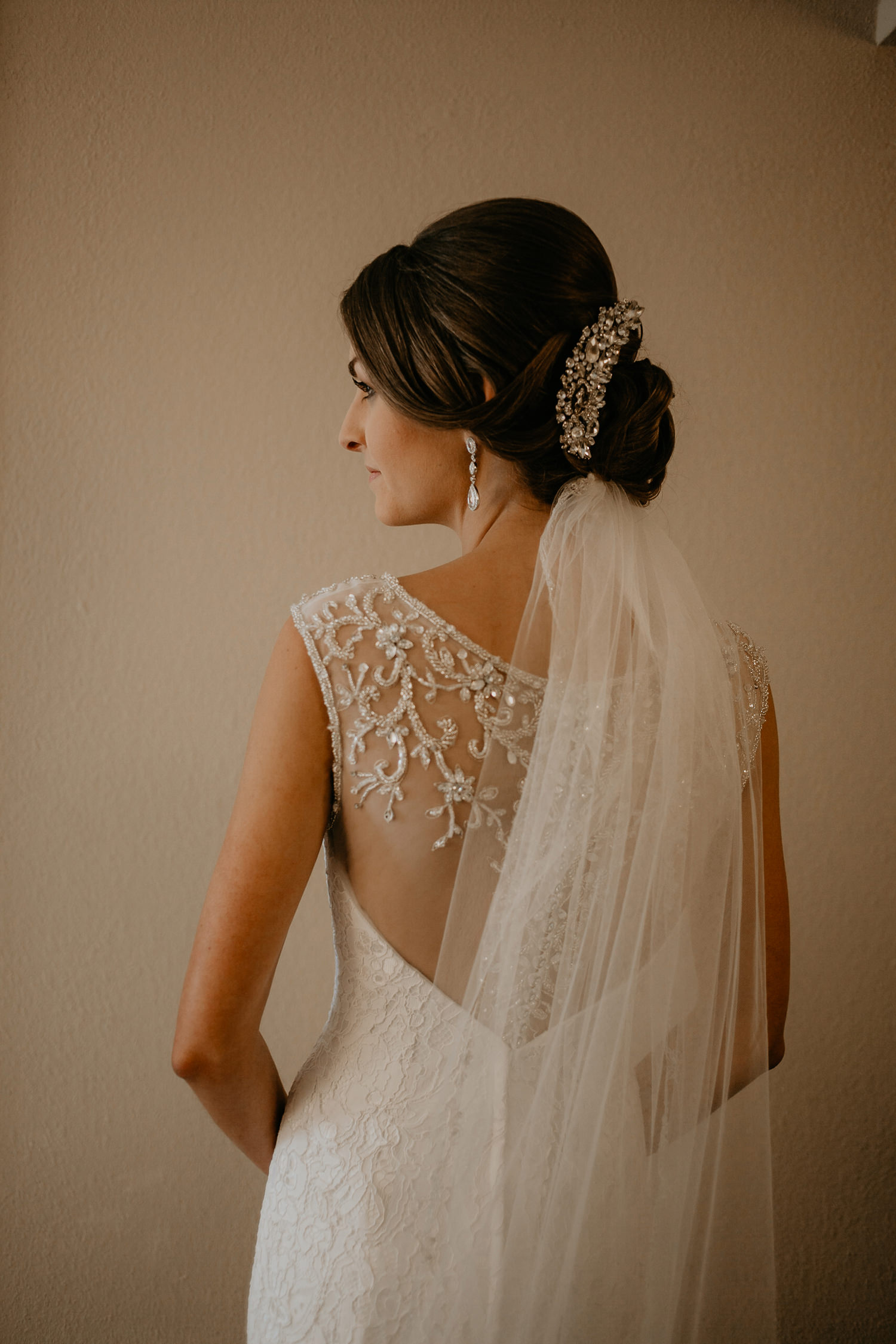 closeup of the bride's back of her dress as she looks sideways