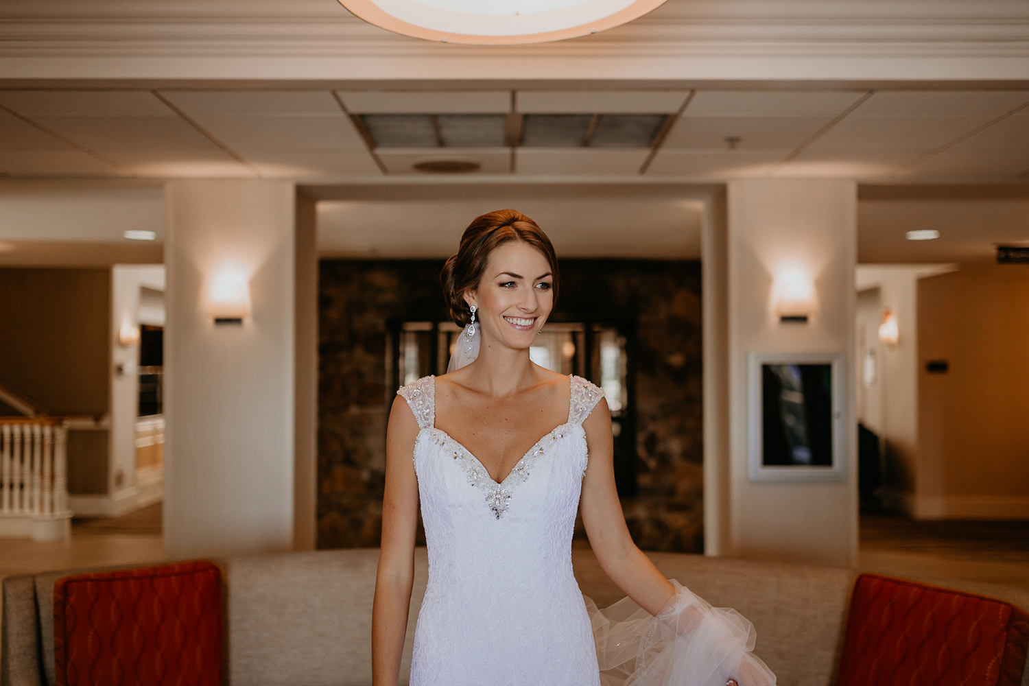 bride in Lake Mary Hilton hotel lobby holding her veil smiling at someone off camera