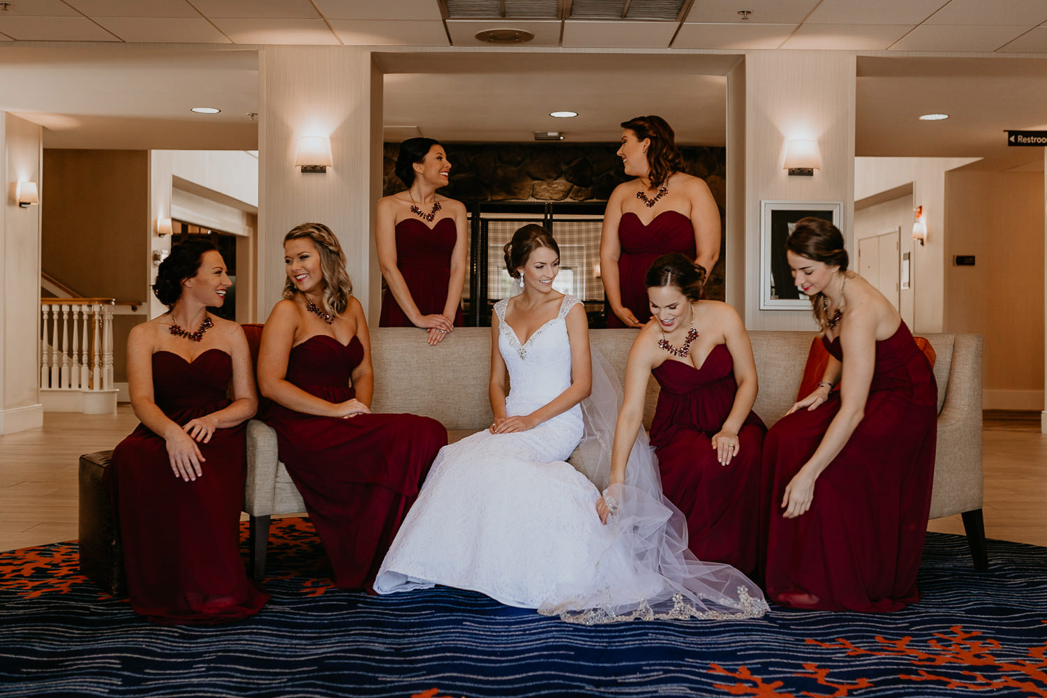 bride and bridesmaids sitting on hotel lobby couch