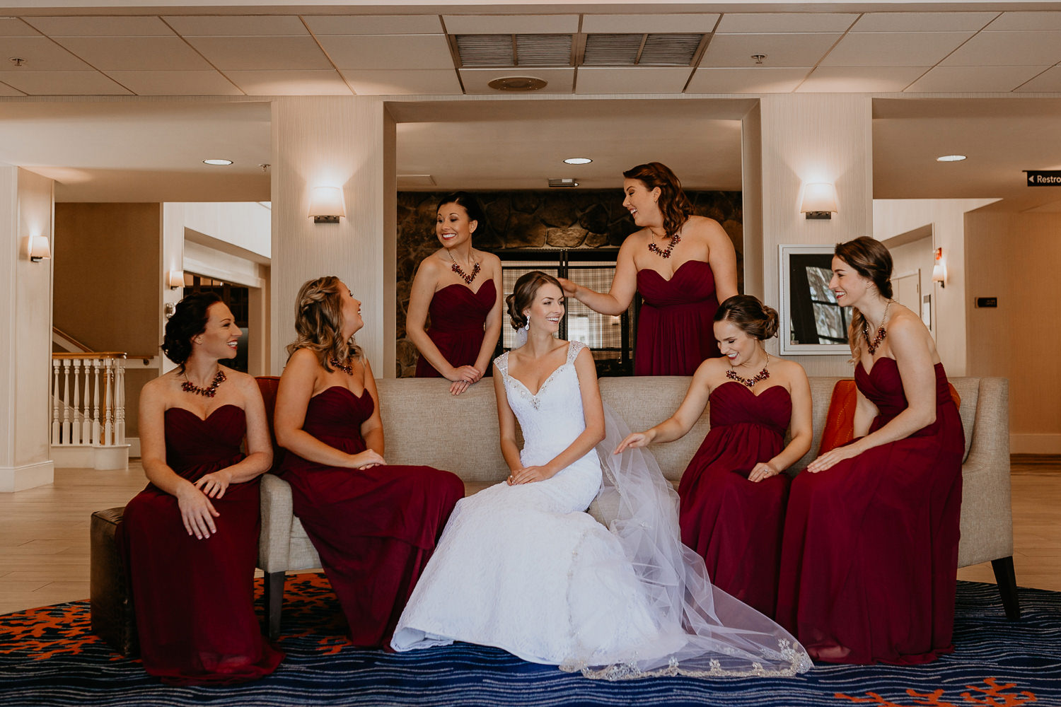 bride and bridesmaids sitting on hotel lobby couch all laughing