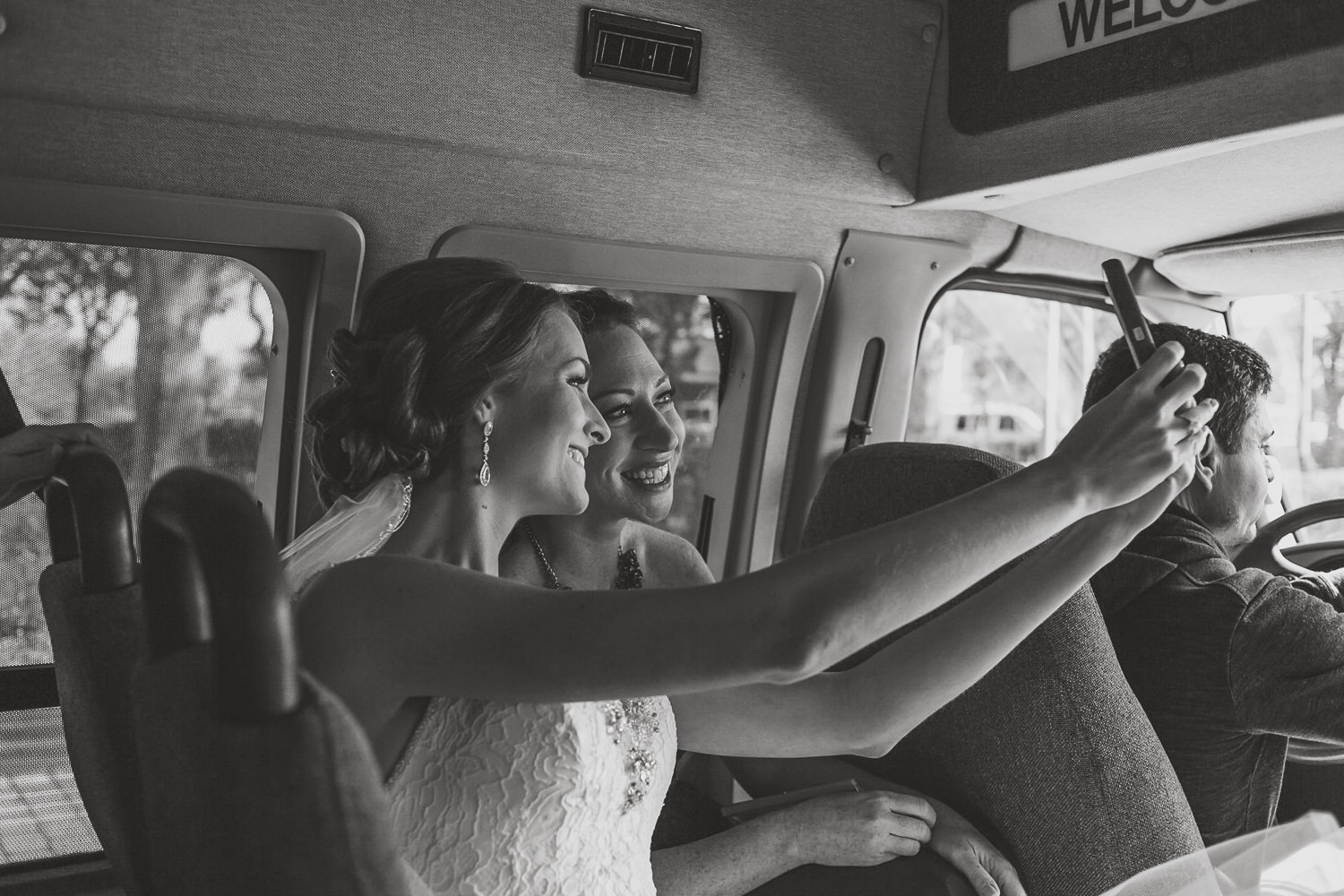 bride and bridesmaid sitting in front row of bus taking a selfie