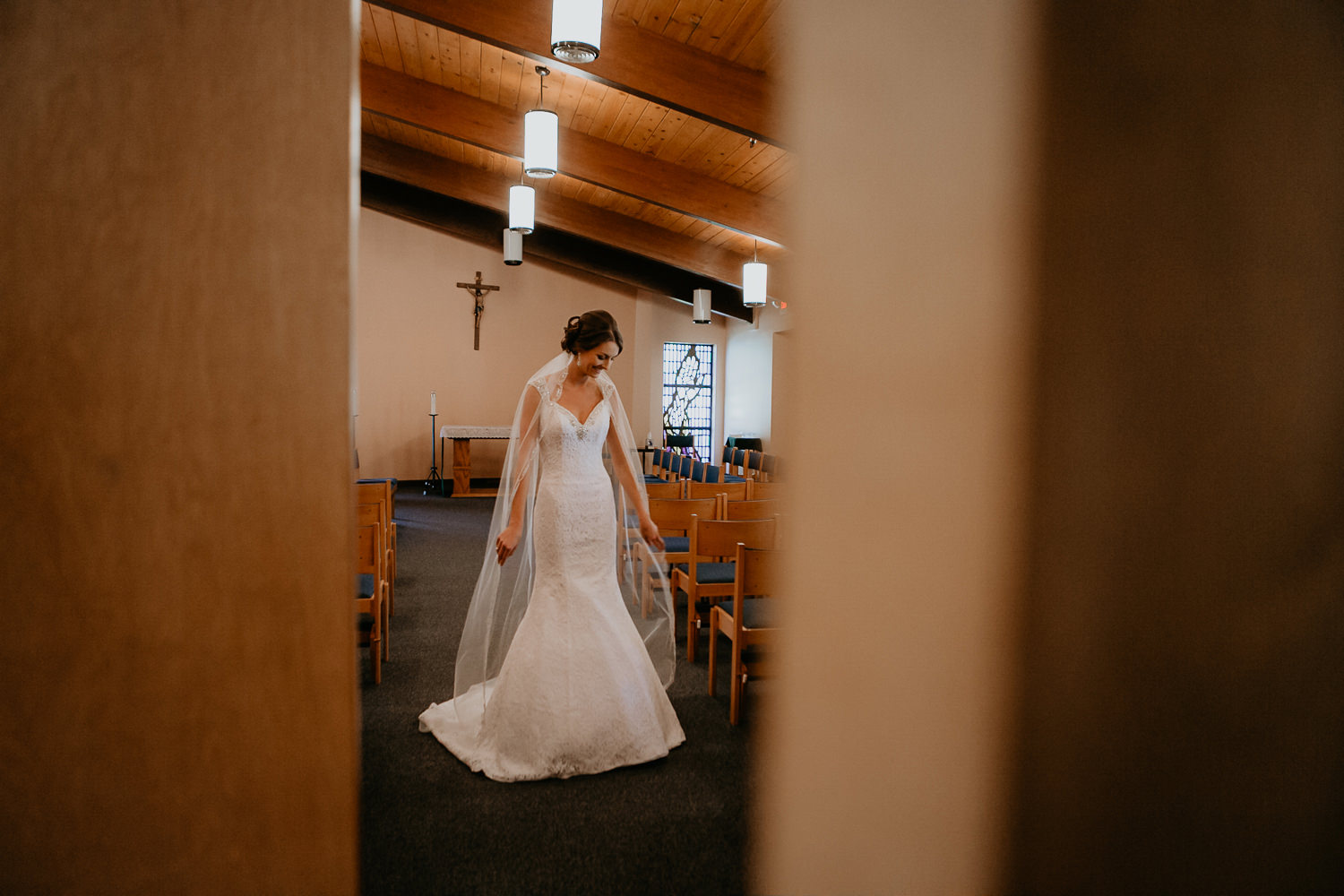 sneaky picture of bride smiling down in church room