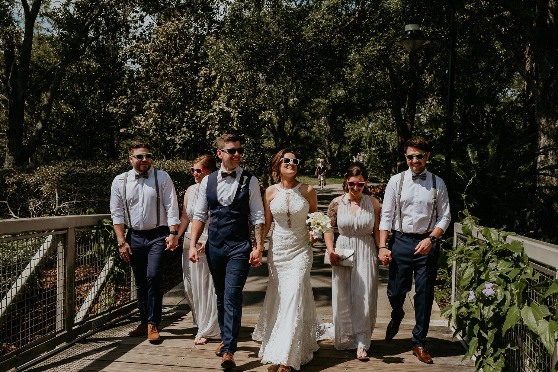 bridal party wearing sunglasses walking on hard rock resort bridge