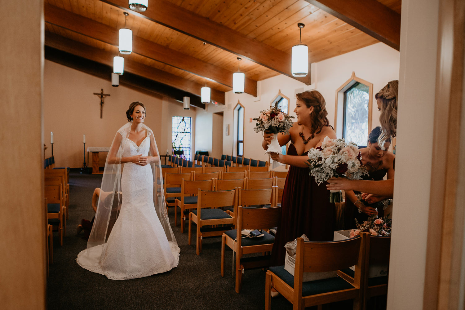 bride smiling inside church room bridesmaids drying their flowers