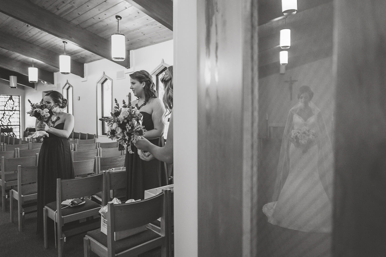 black and white reflection of bride looking down thru church door