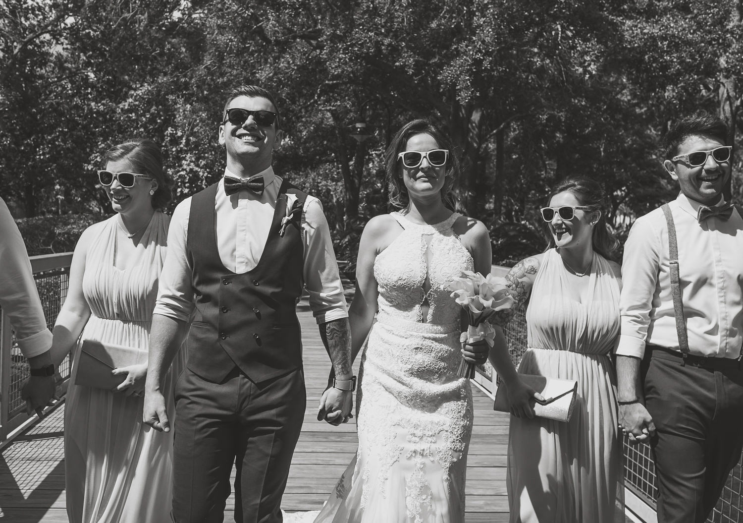 black and white close up of bridal party walking on bridge all wearing sunglasses and laughing