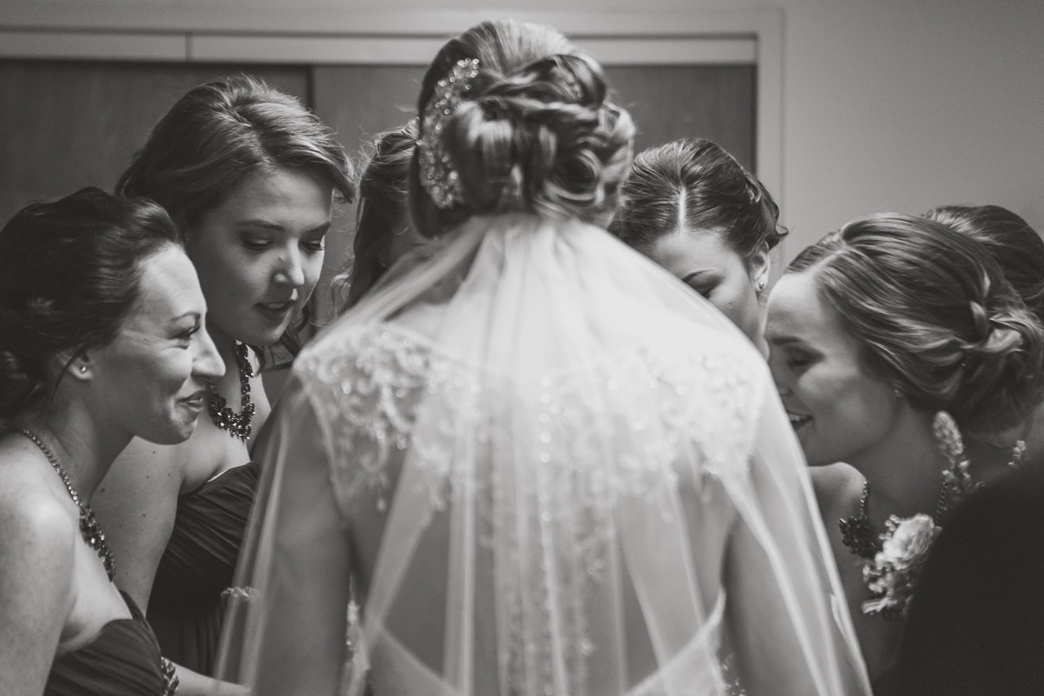 black and white close up of bride and bridesmaids huddled and praying