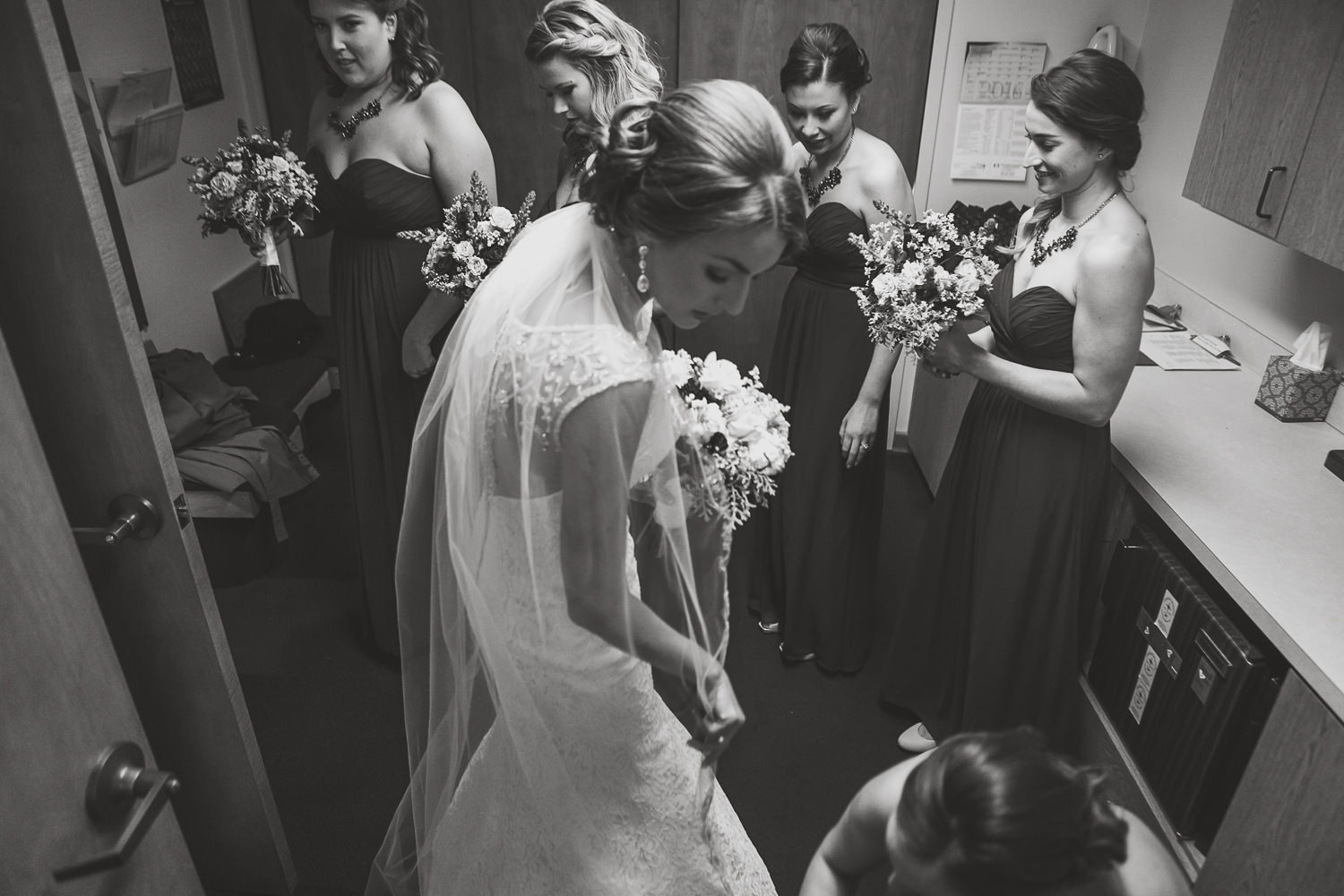 black and white bride looking down as bridesmaid fixes her dress