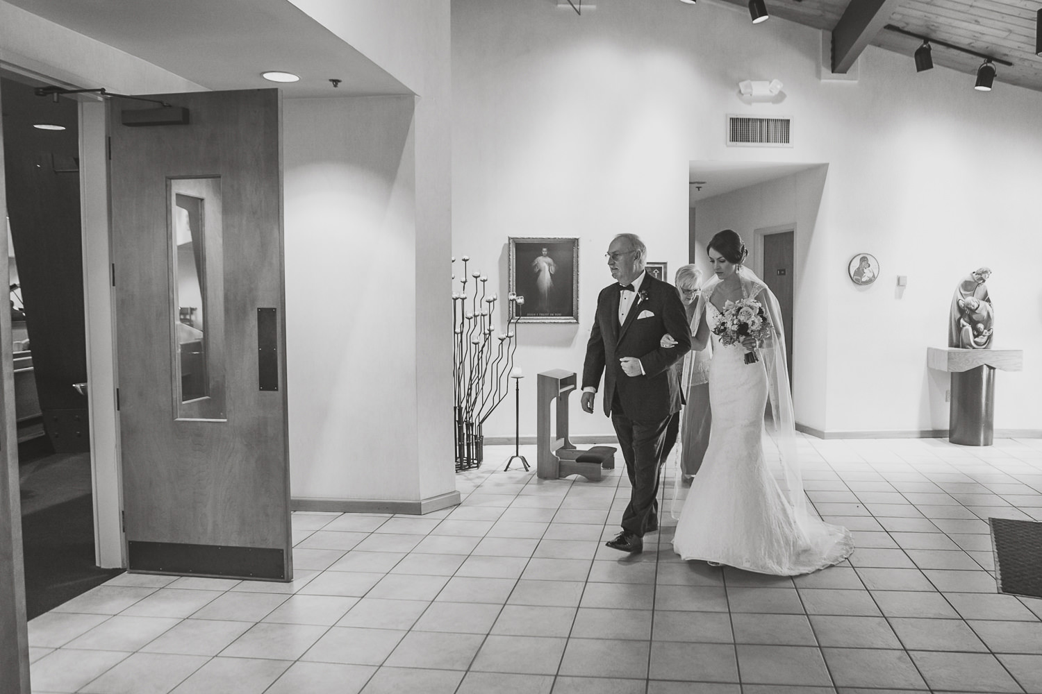 black and white of church lobby with bride and groom starting to walk