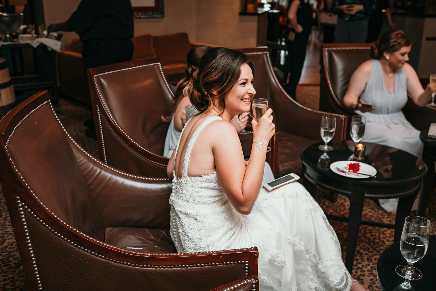 bride and bridesmaids sitting on leather chairs holding Champagne glasses
