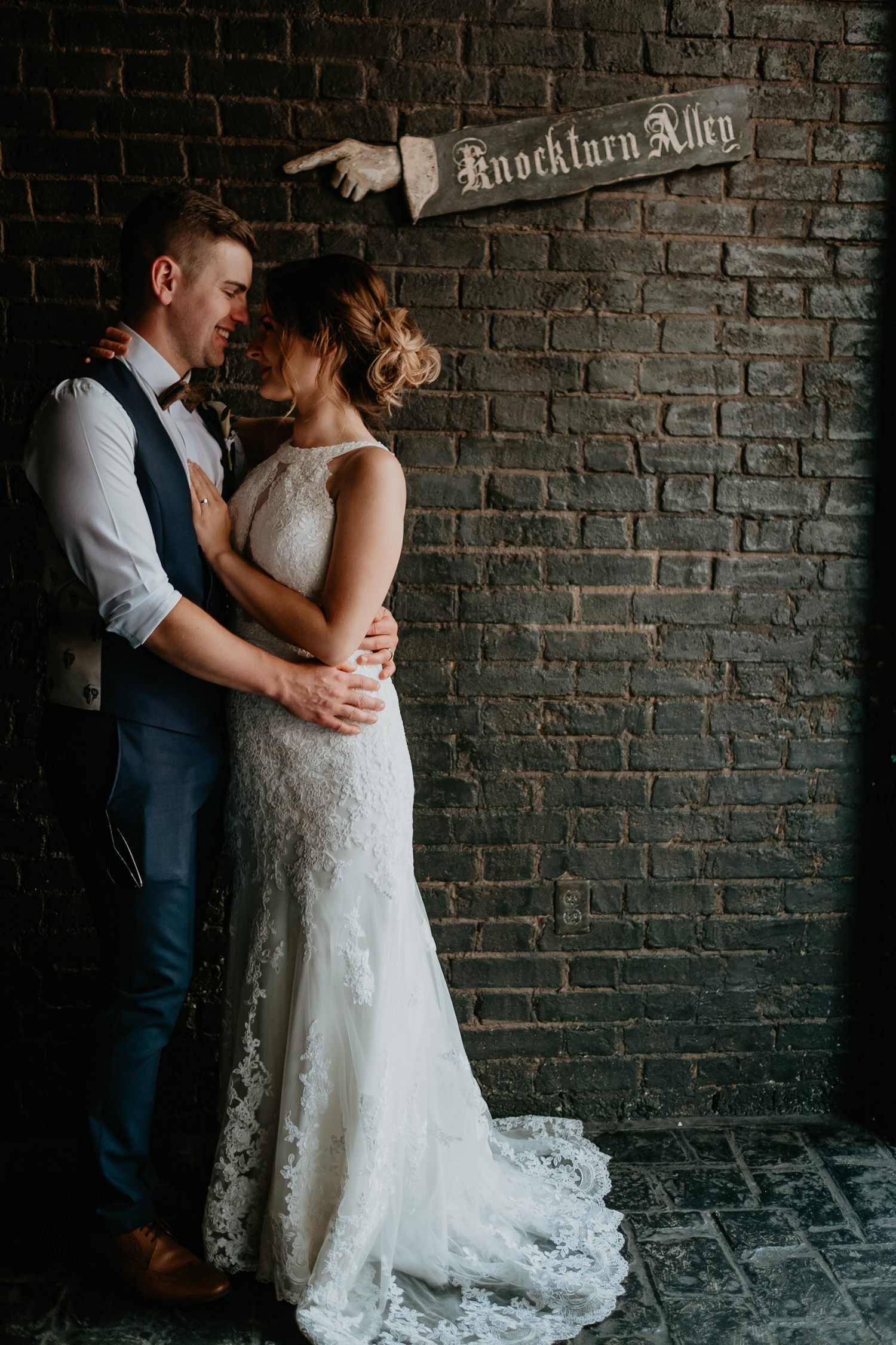 newlyweds facing each other in front of brick wall with Knockturn Alley sign pointing at them