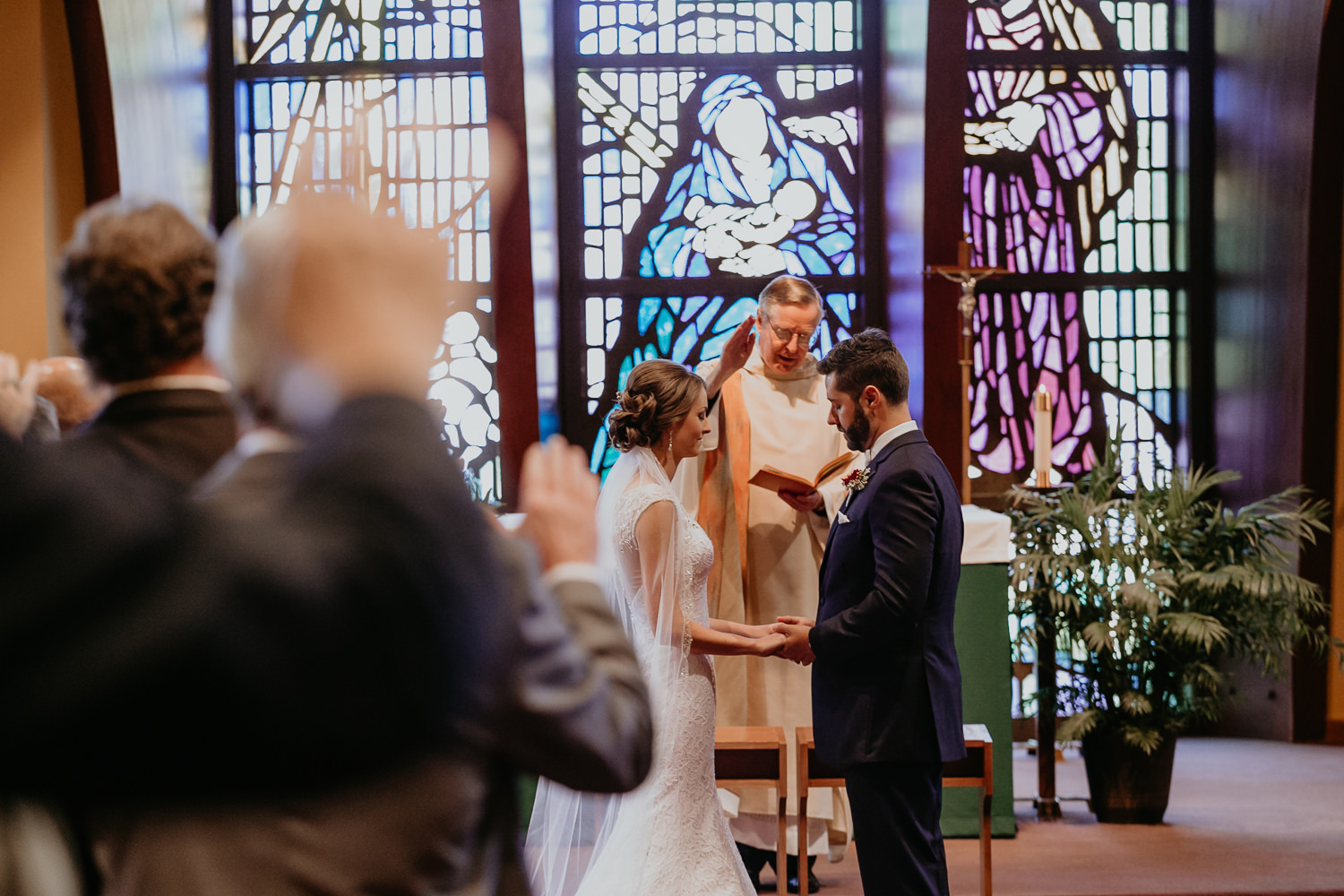 bride and groom holding hands at the altar, guests praying with hands in the air