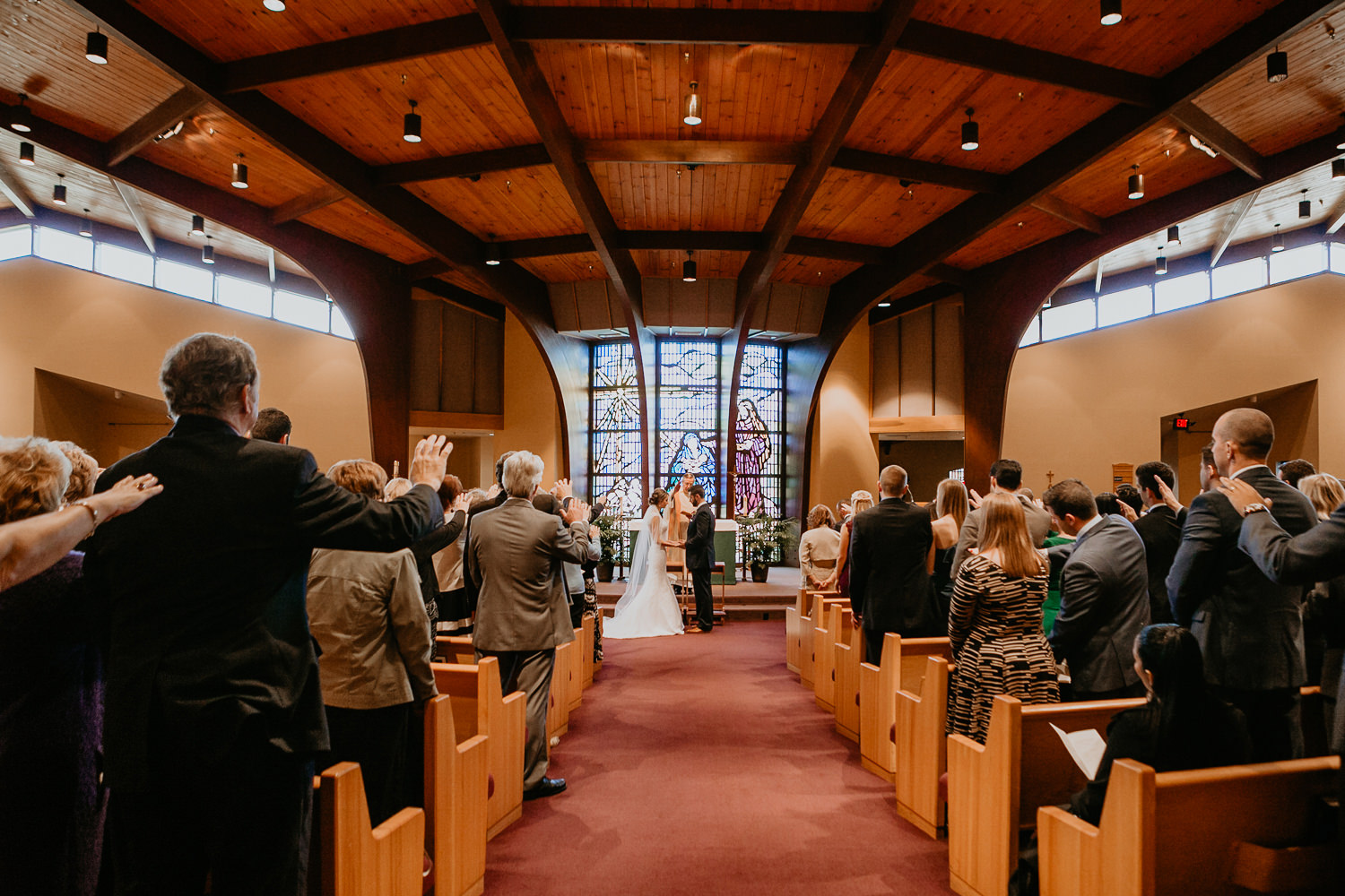 wide view of newlyweds holding hands all guests with hands up blessing the couple