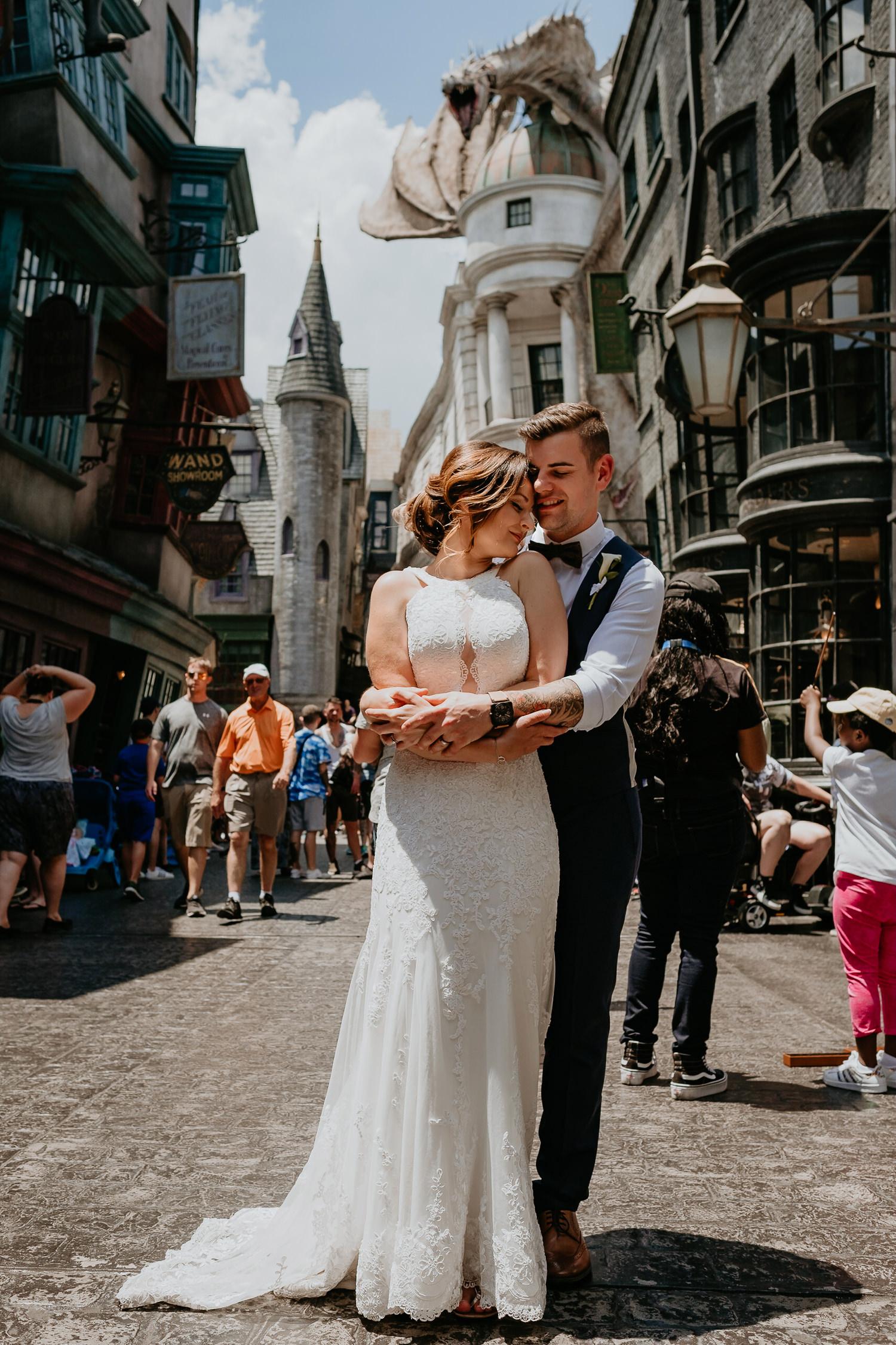 groom hugging bride from behind in front of Gringotts Bank
