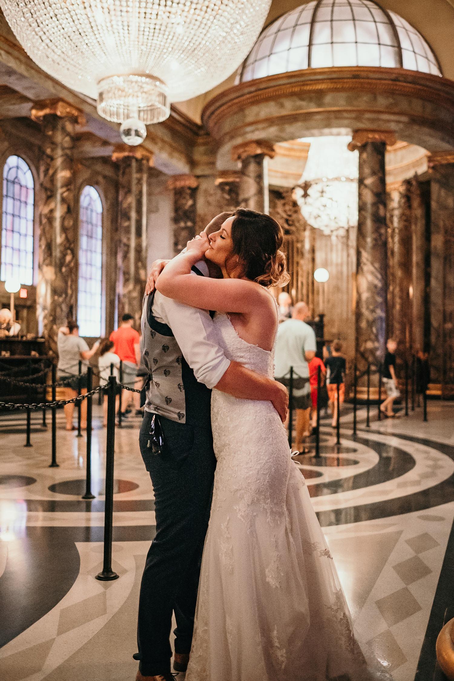 newlyweds hugging intimately inside gringotts bank