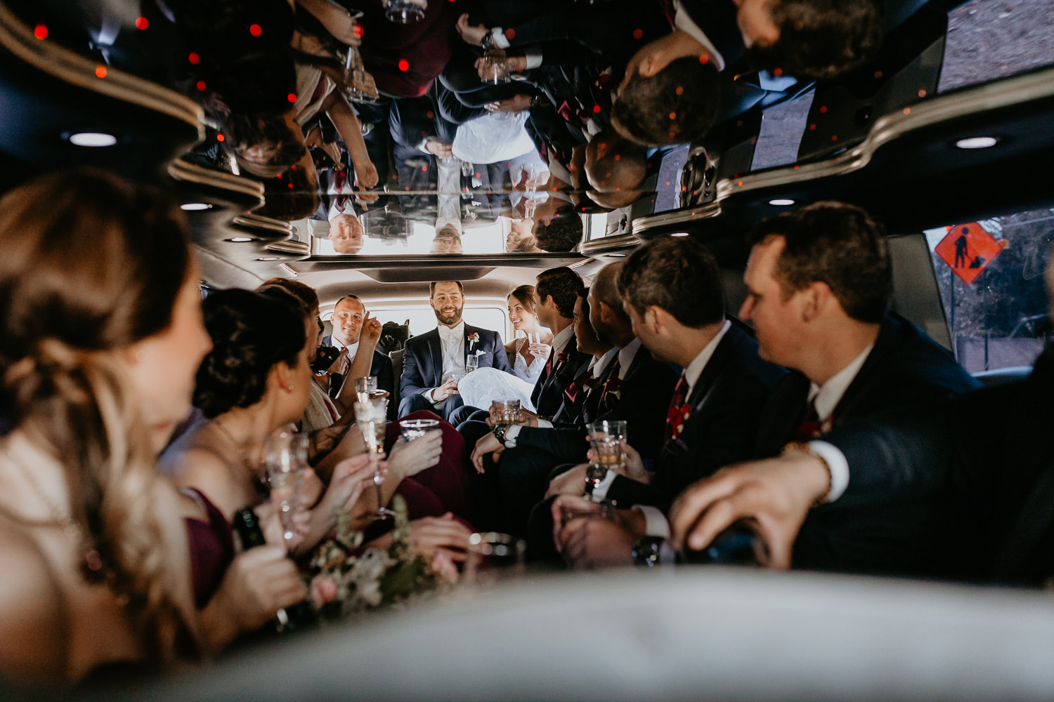inside the limousine entire bridal party on the sides newlyweds in the middle