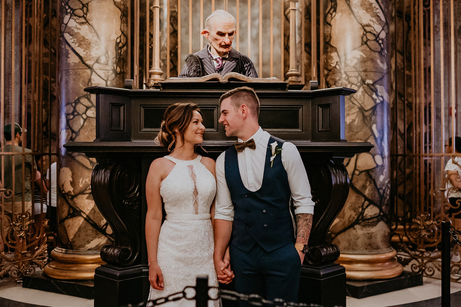 bride and groom side by side holding hands looking at each other with bank elf behind