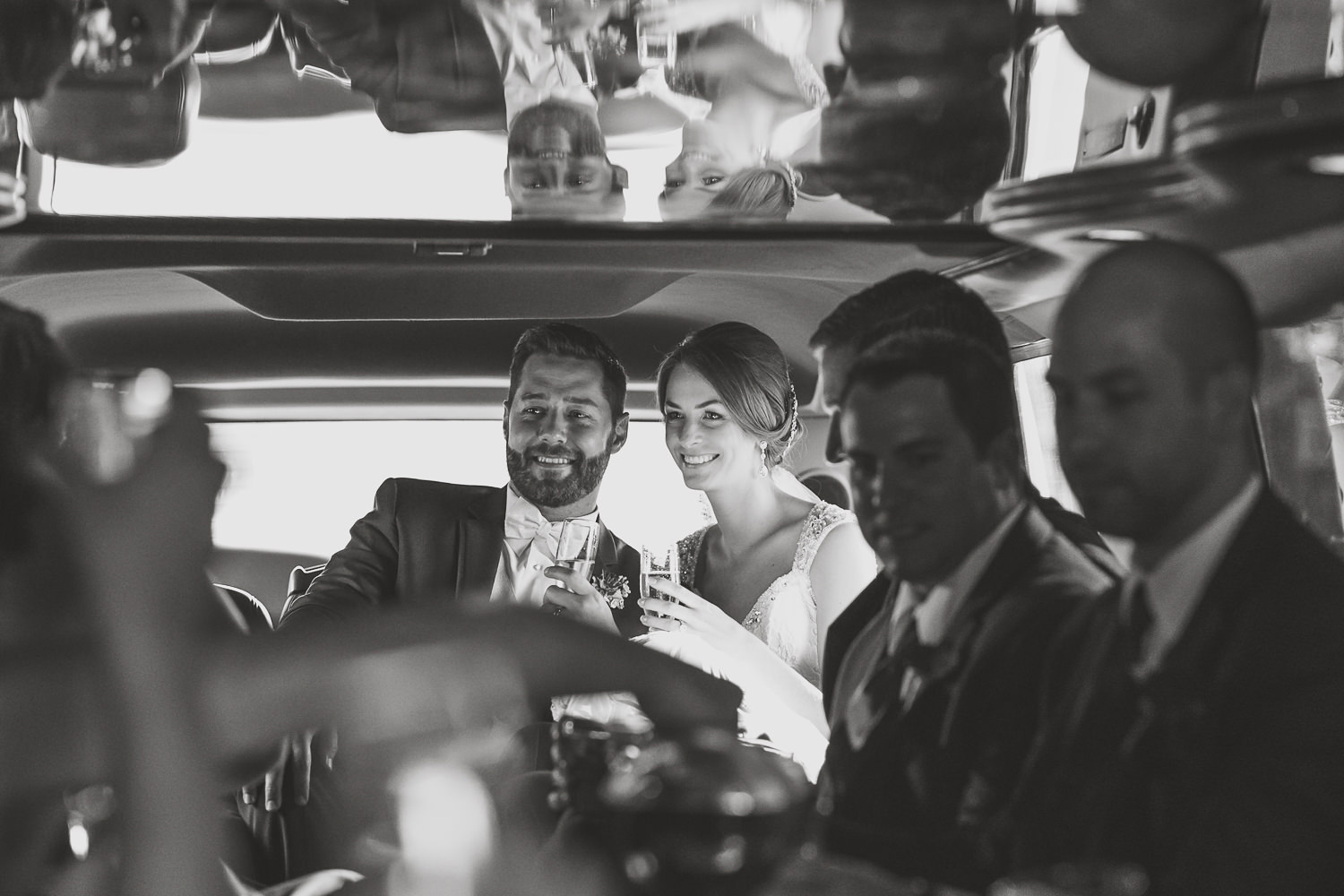 closeup of newlyweds inside limousine holding champagne glasses