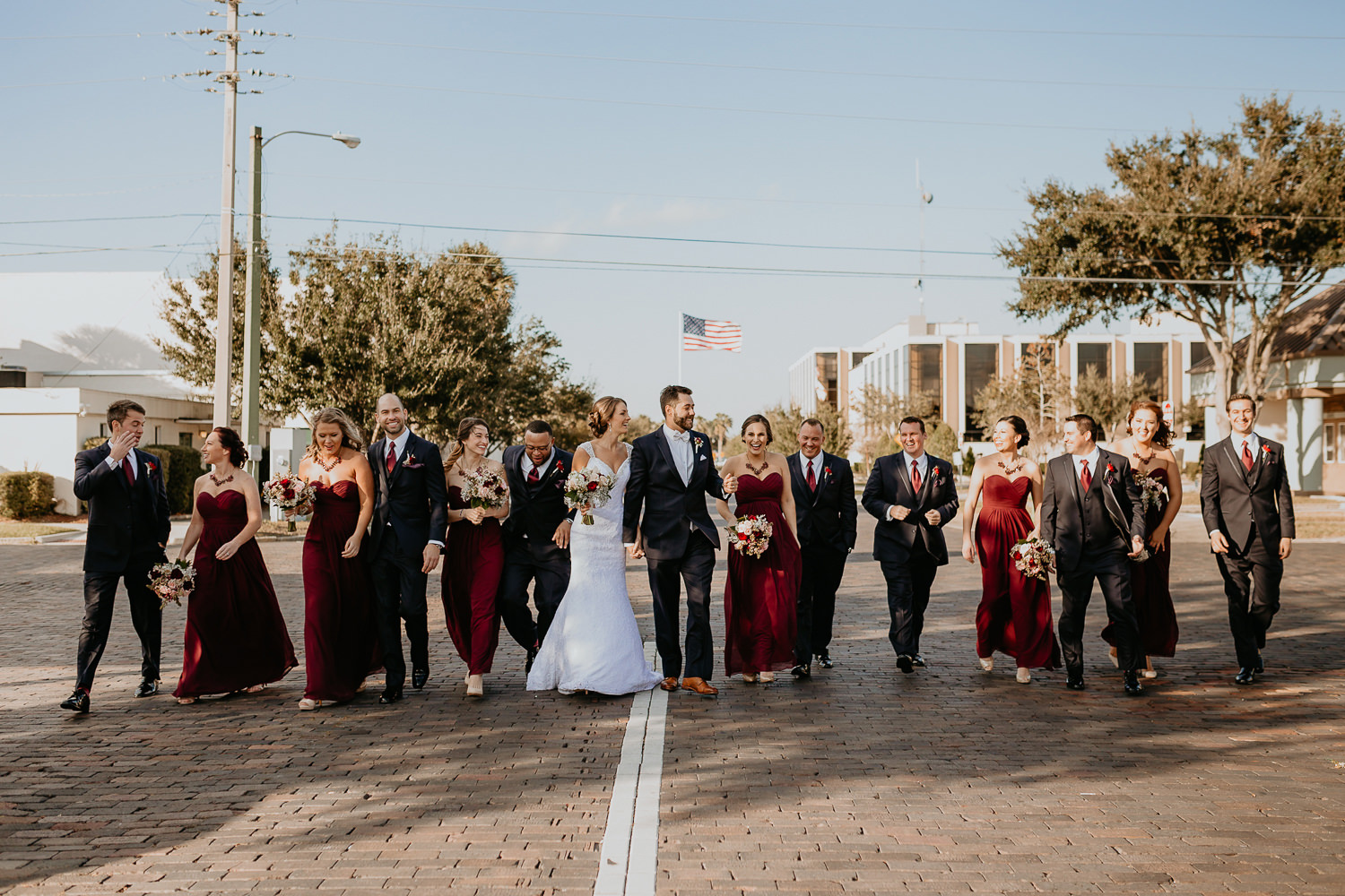 bridal party lined up walking down cobblestone street in Sanford