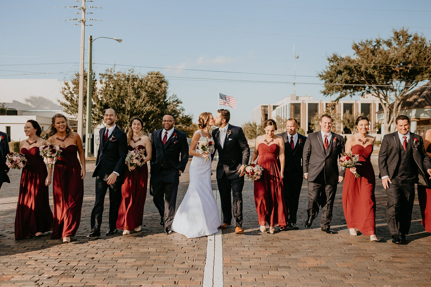 bridal party mixed males and females newlyweds kissing in the middle on cobblestone