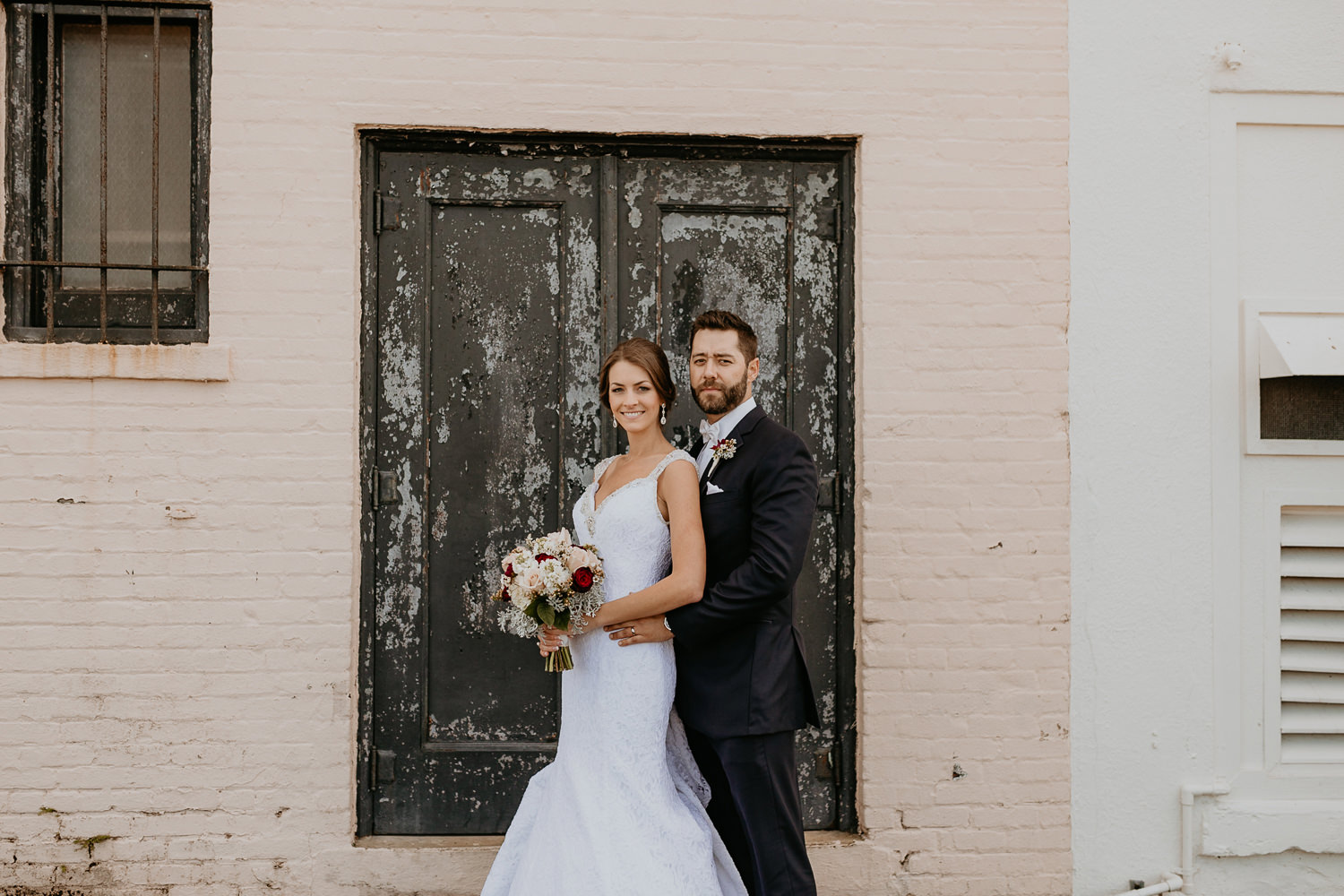 newlyweds posing in front of paint deteriorating wooden doors