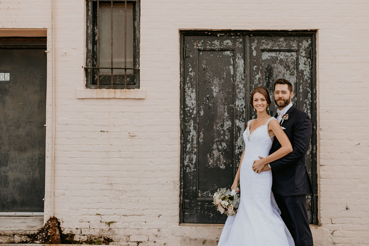 groom behind the bride, she's holding her flowers, posing in front of wooden door