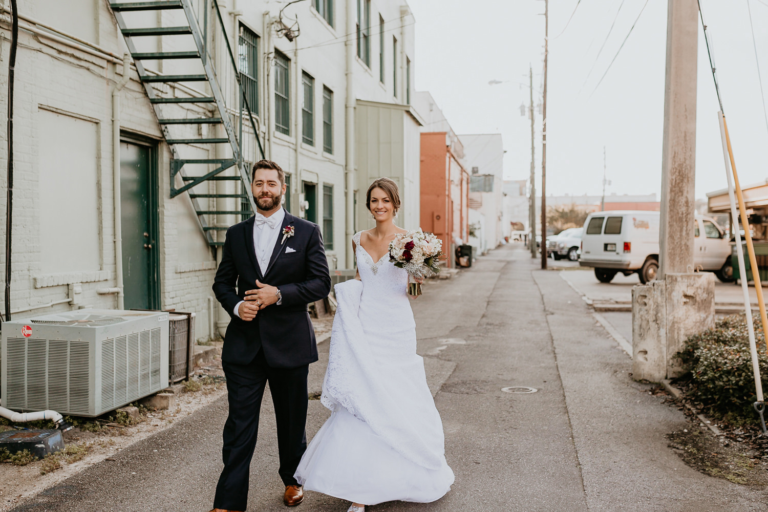 bride and groom walking in middle of downtown sanford alley