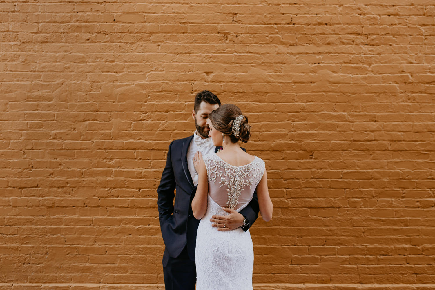 newlyweds posing in front of yellow brick wall