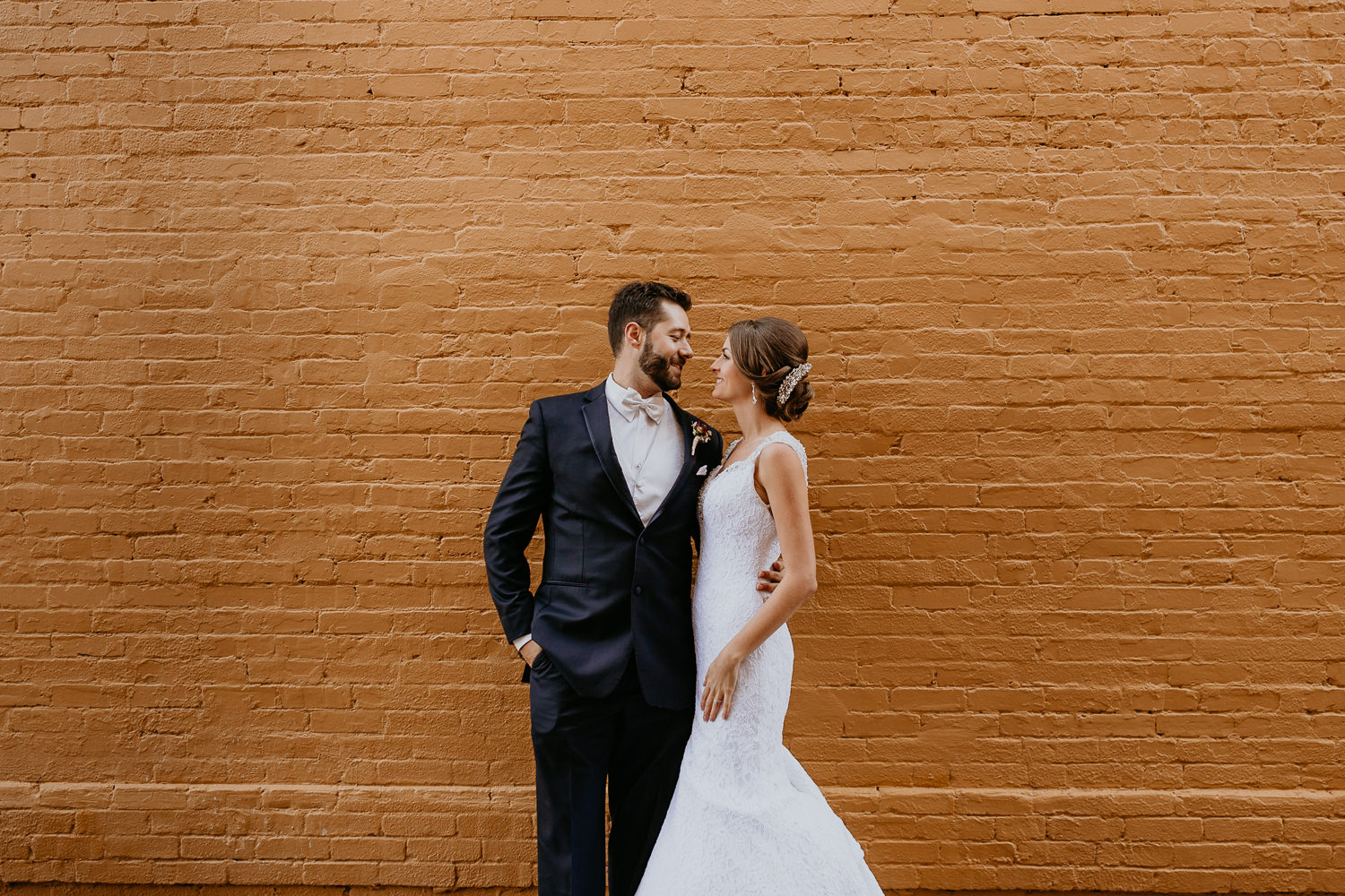 bride and groom smiling at each other in front of yellow wall