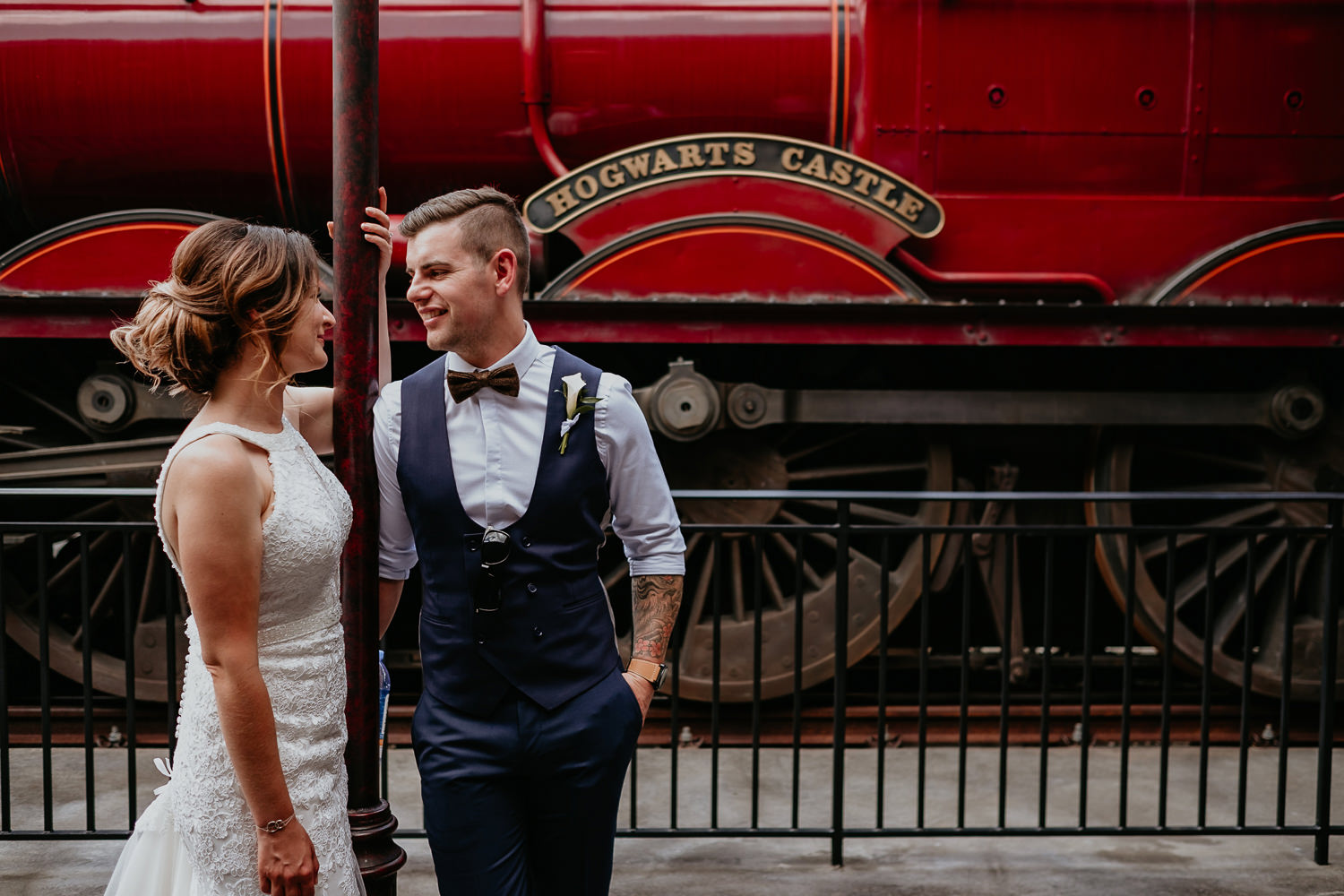 bride and groom posing in front of red Hogwarts Express train