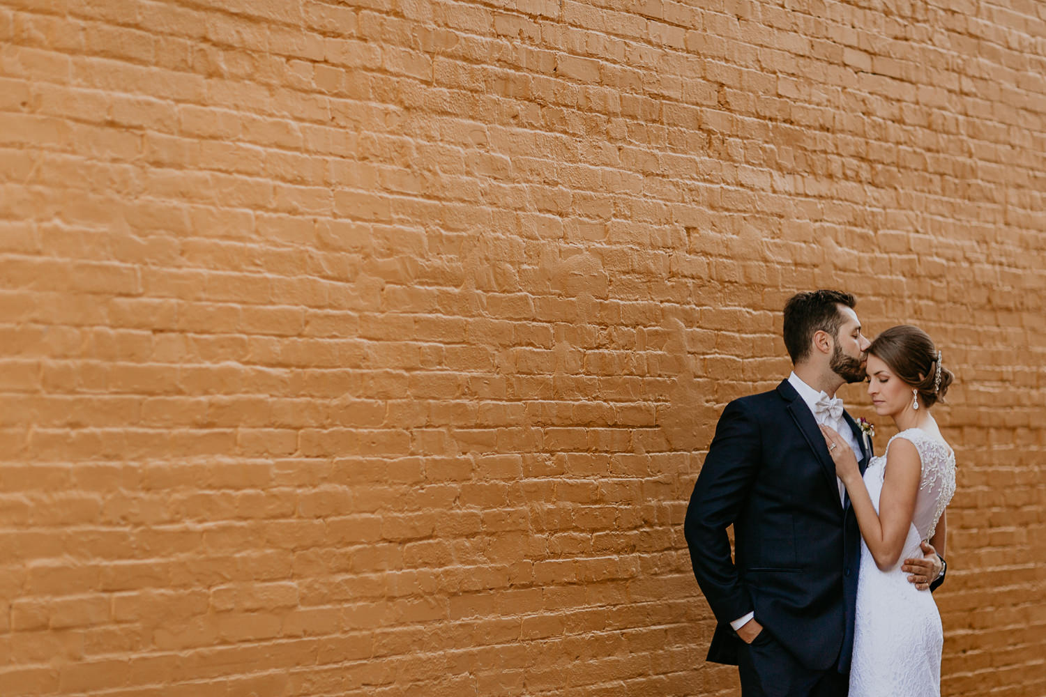 groom kissing bride's forehead in front of yellow brick wall
