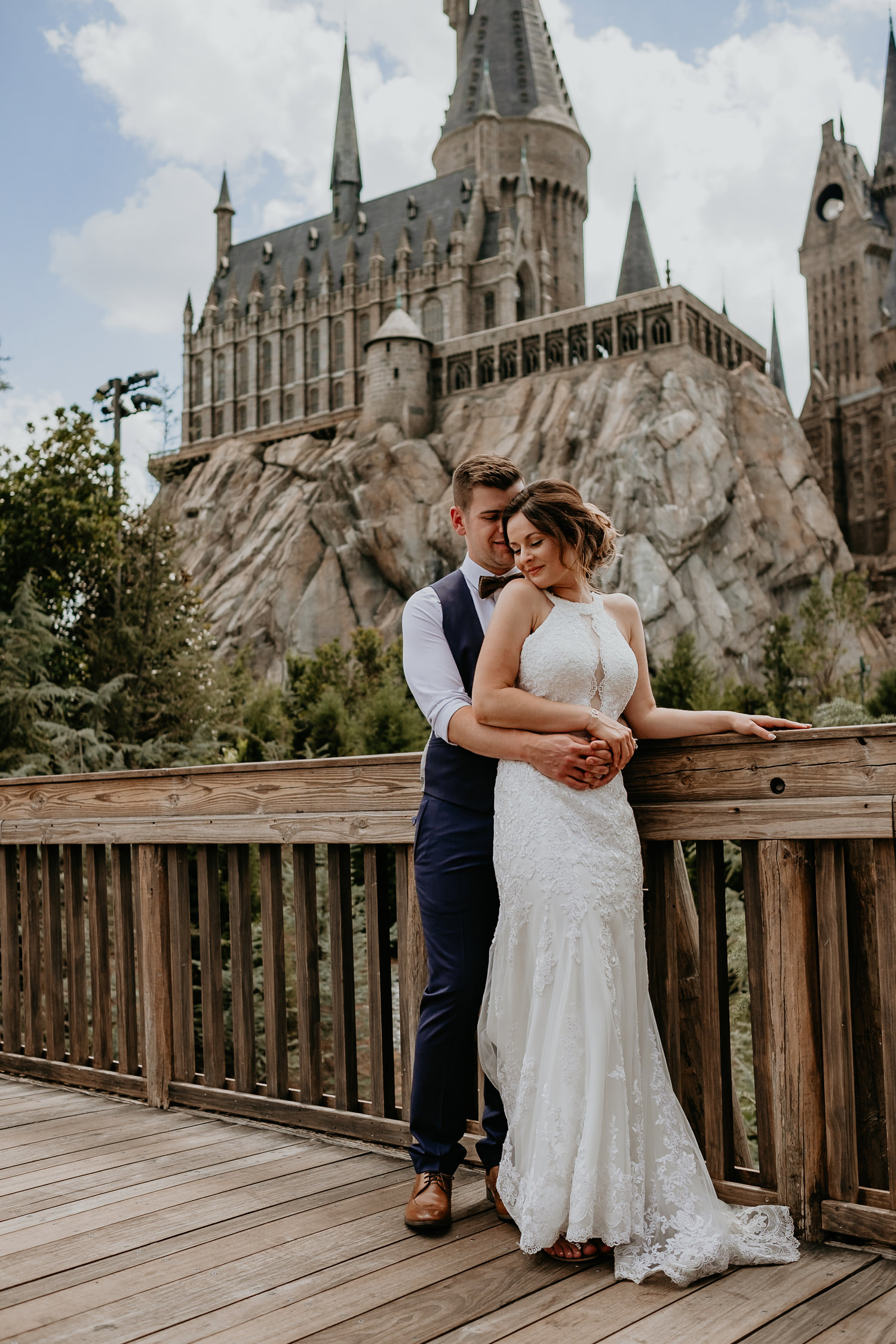 groom hugging bride from behind on bridge in front of hogwarts castle