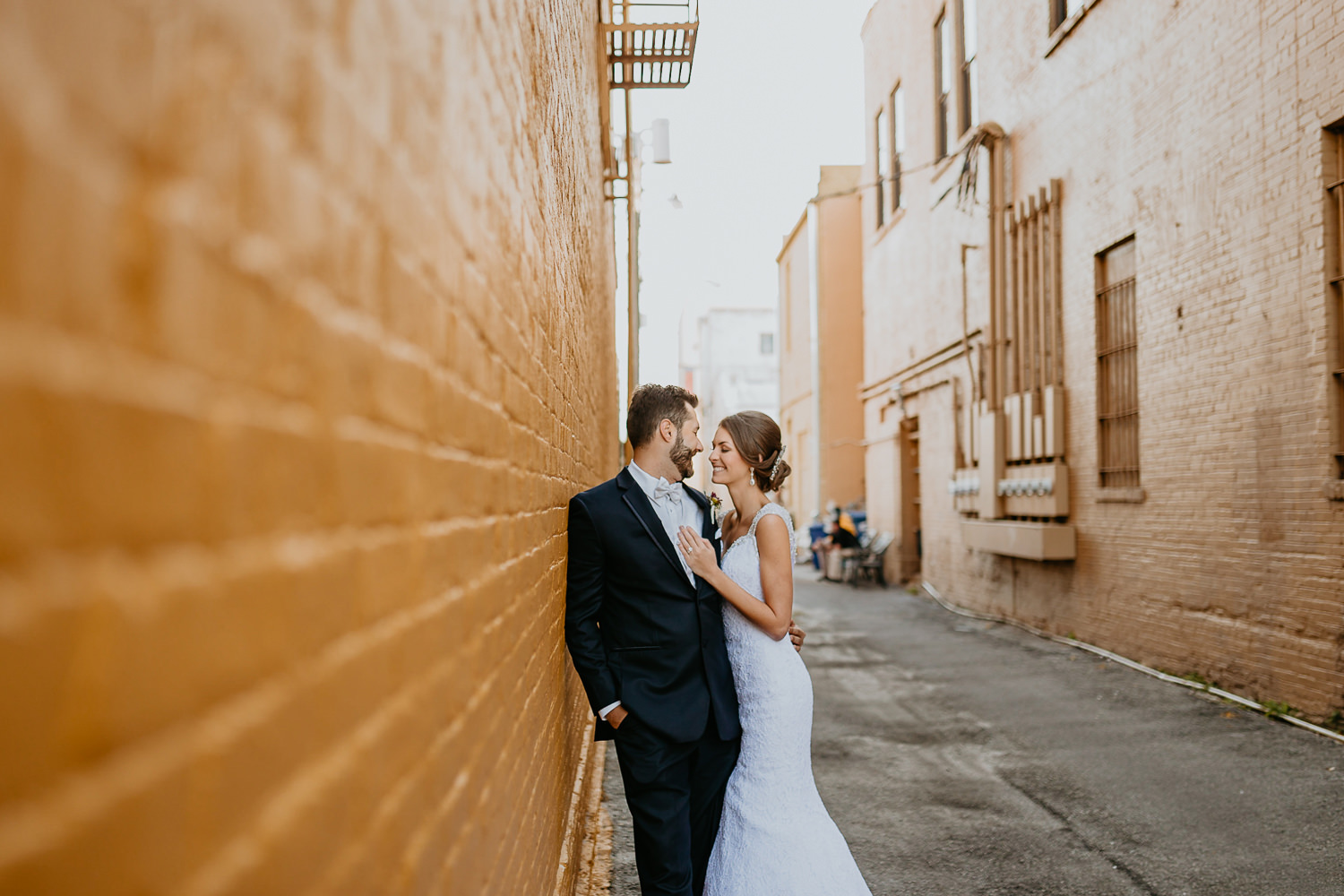 wide view of newlyweds smiling at each other in sanford back alley