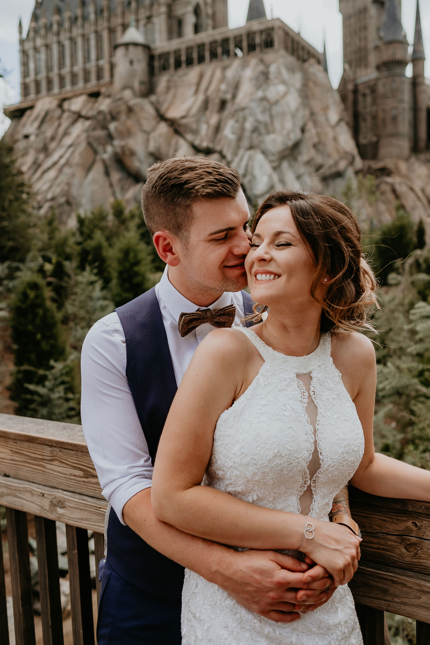 close up of groom behind bride kissing her cheek with hogwarts castle in background
