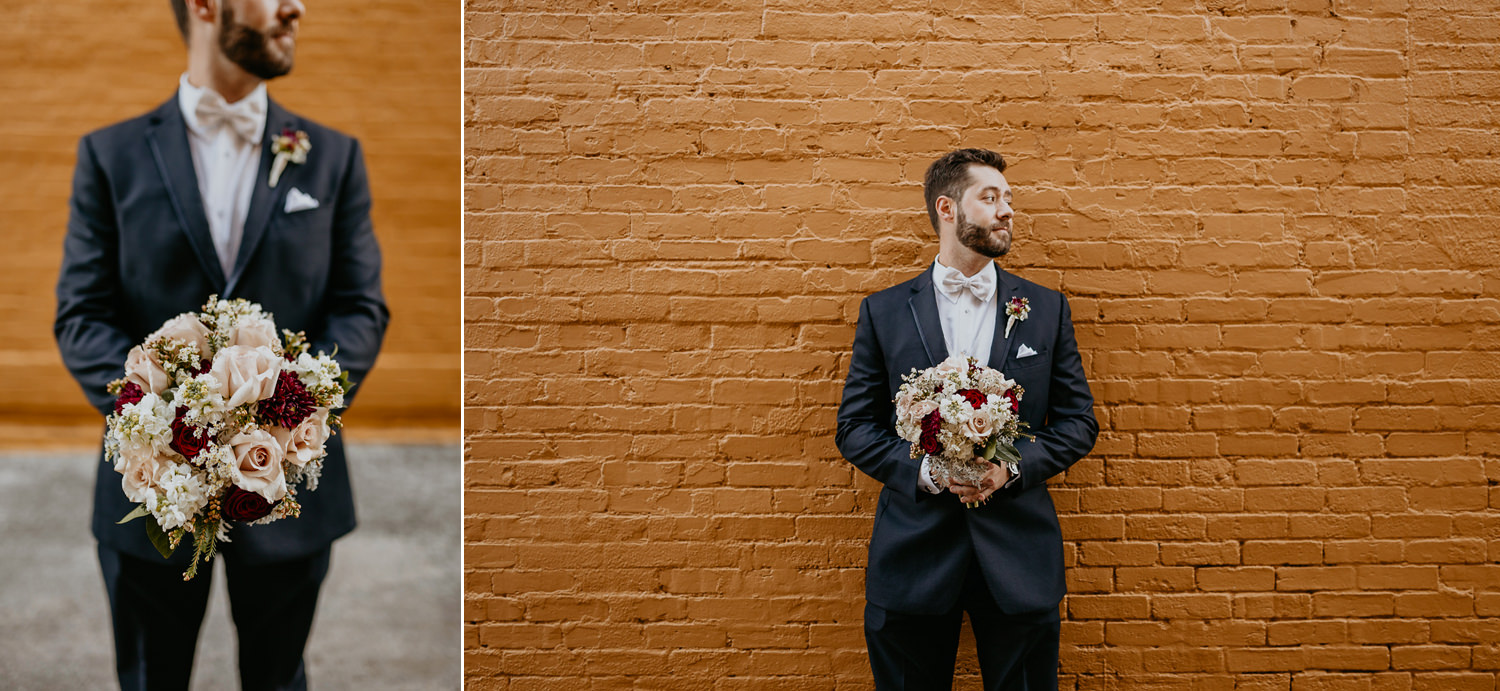 groom holding the bride's bouquet in front of yellow brick wall