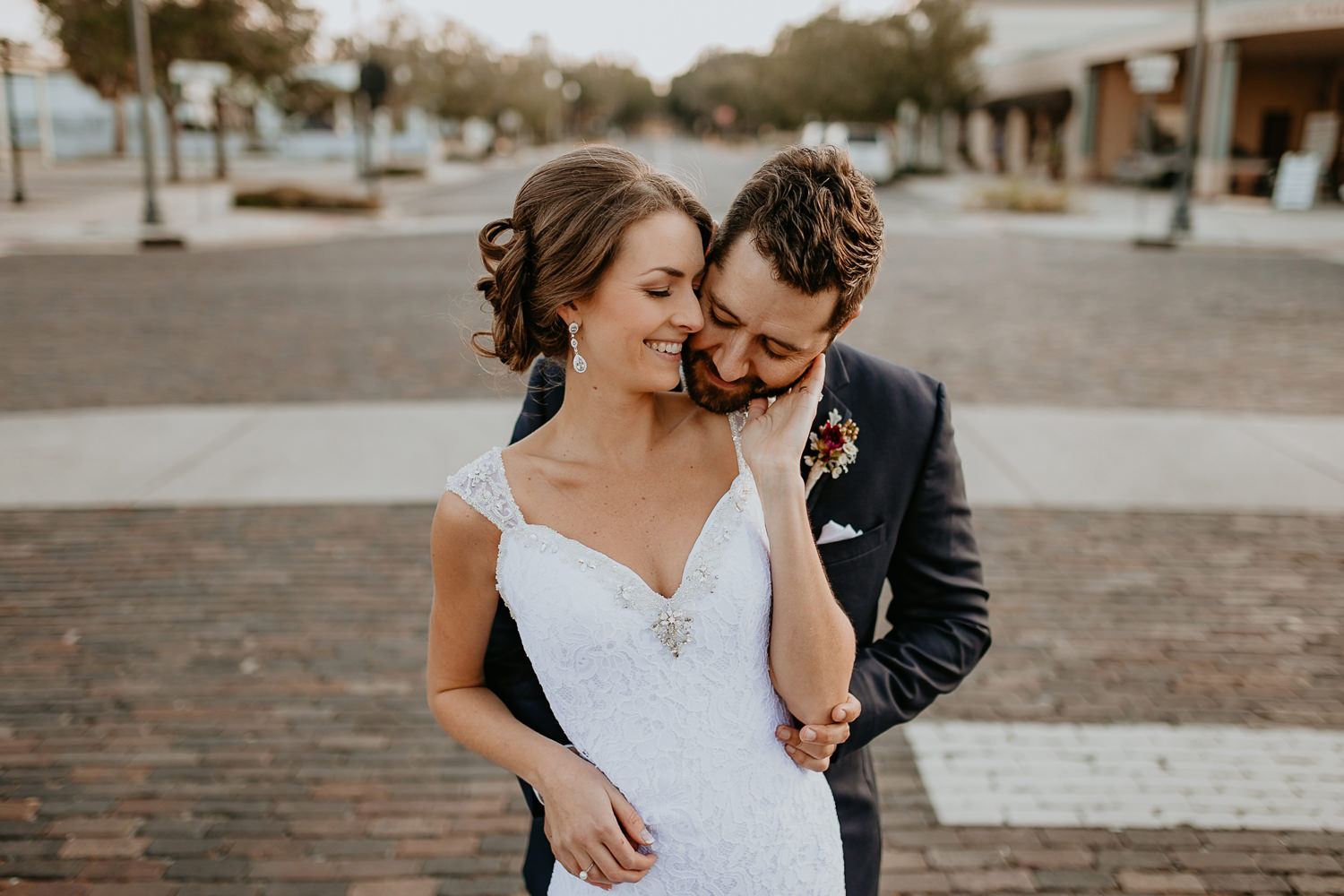 groom hugging bride from being her hand on his cheek on cobblestone road