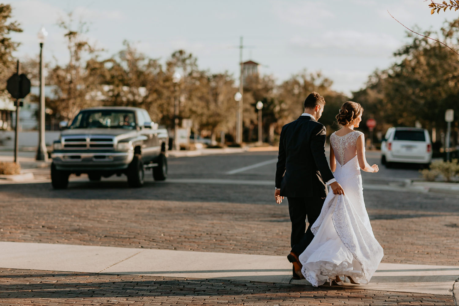 newlyweds walking away from camera on cobblestone road