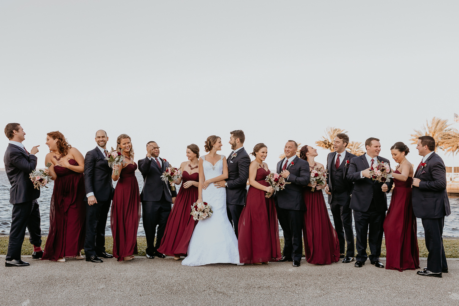 bridal party lined up mixed male and female laughing newlyweds in the middle