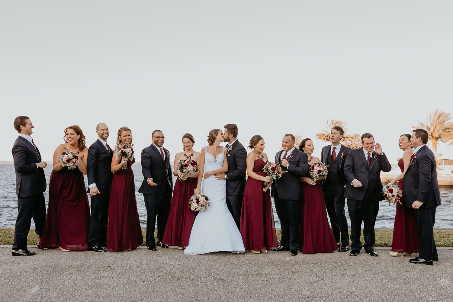 bridal party lined up mixed genders in front of lake newlyweds kissing in the middle