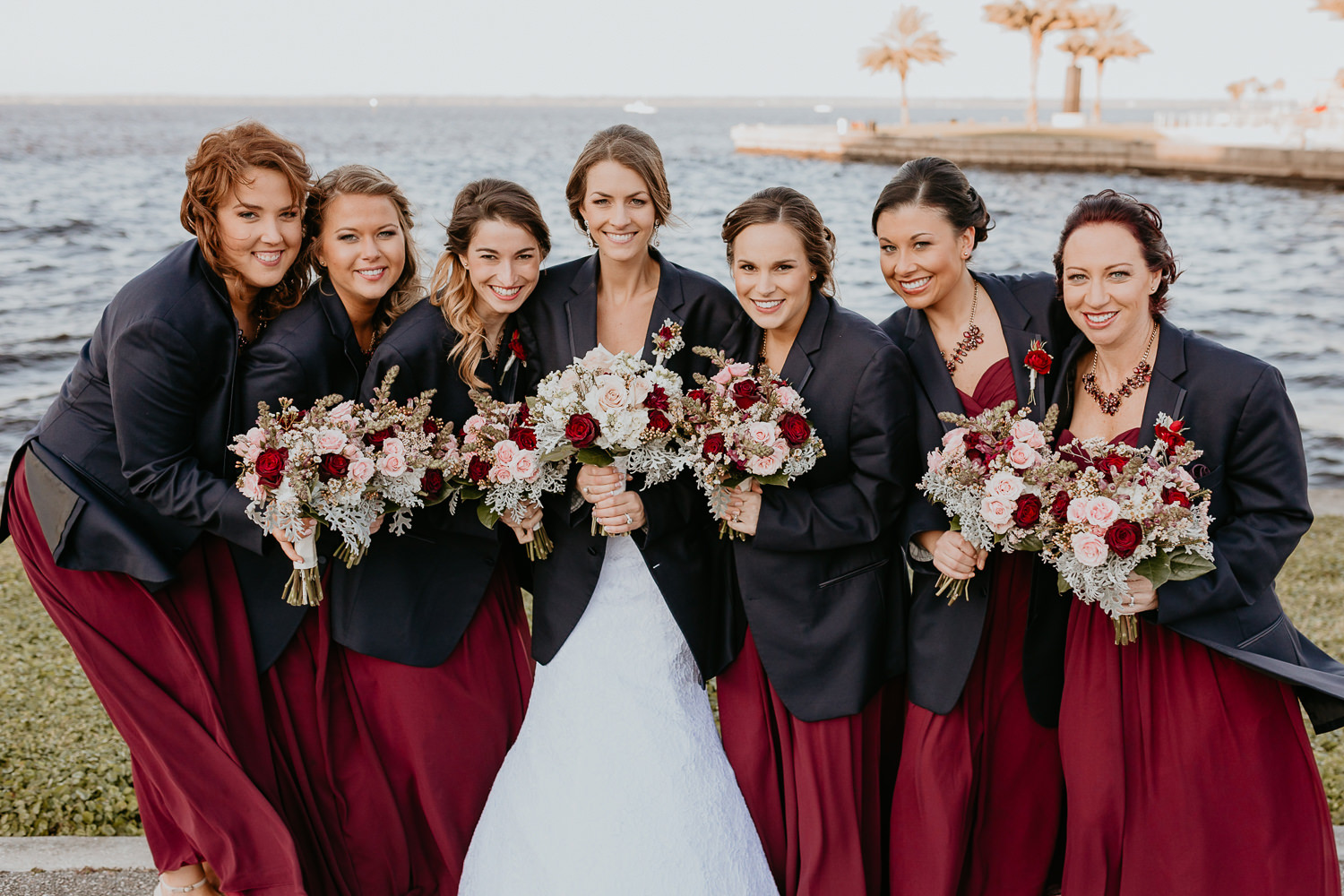 bridesmaids holding their flowers huddled around bride wearing groomsmen jackets