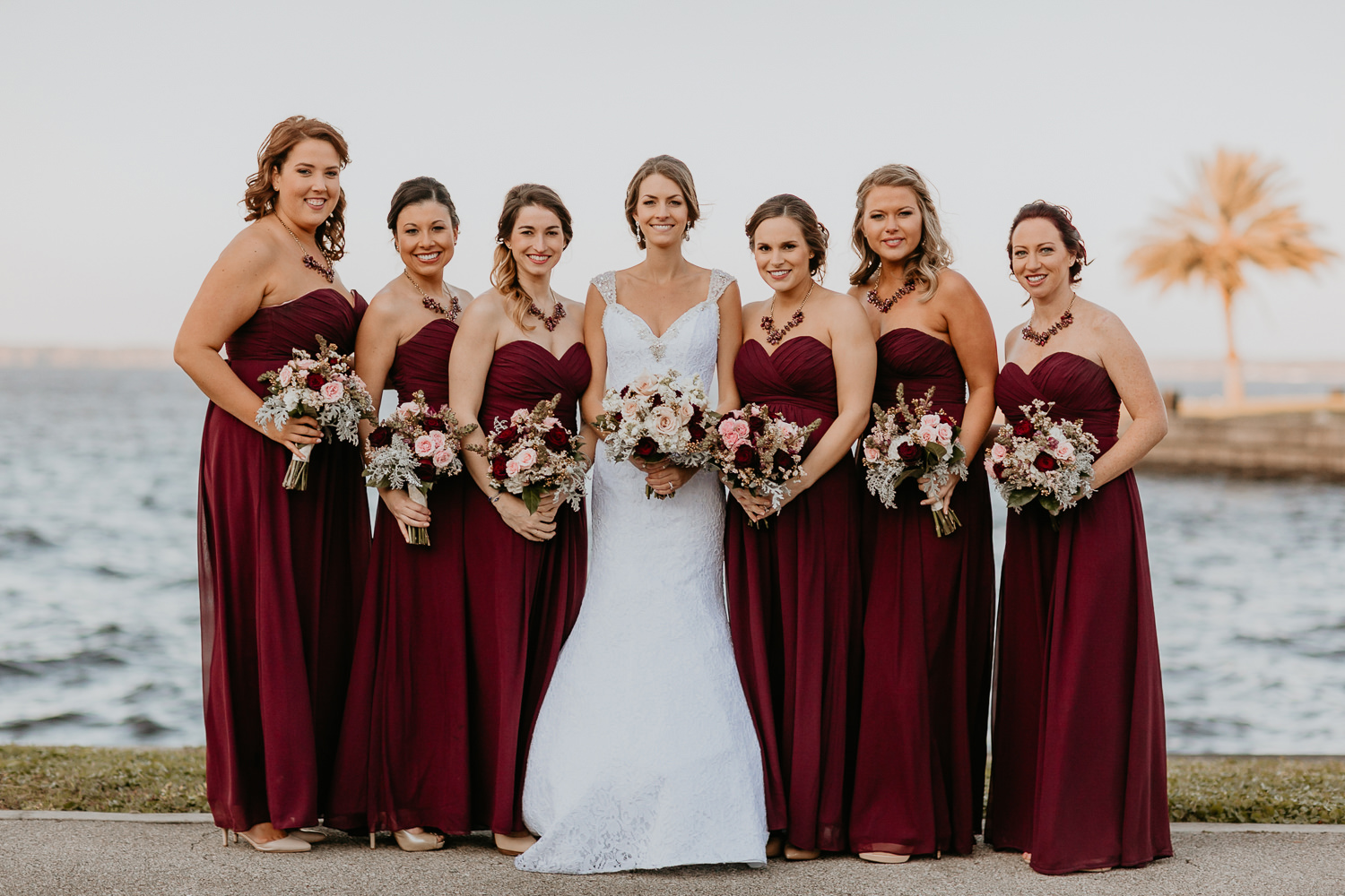 bridesmaids lined up smiling at camera holding bouquets