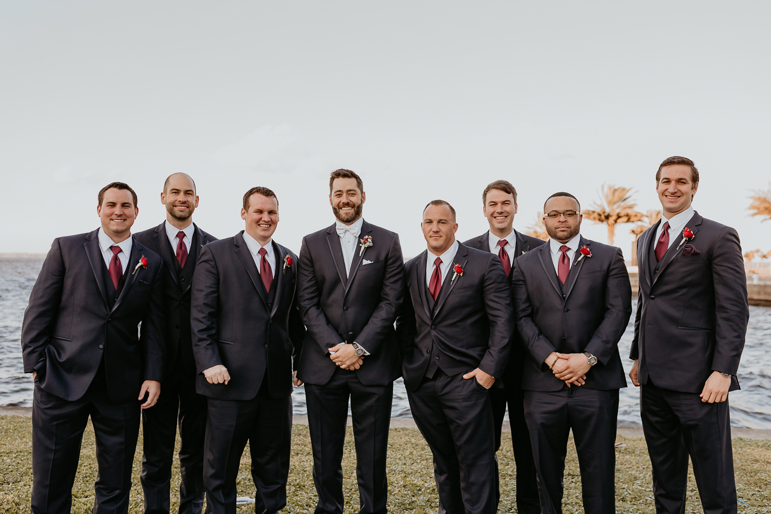 groomsmen lined up smiling at camera with lake in the background