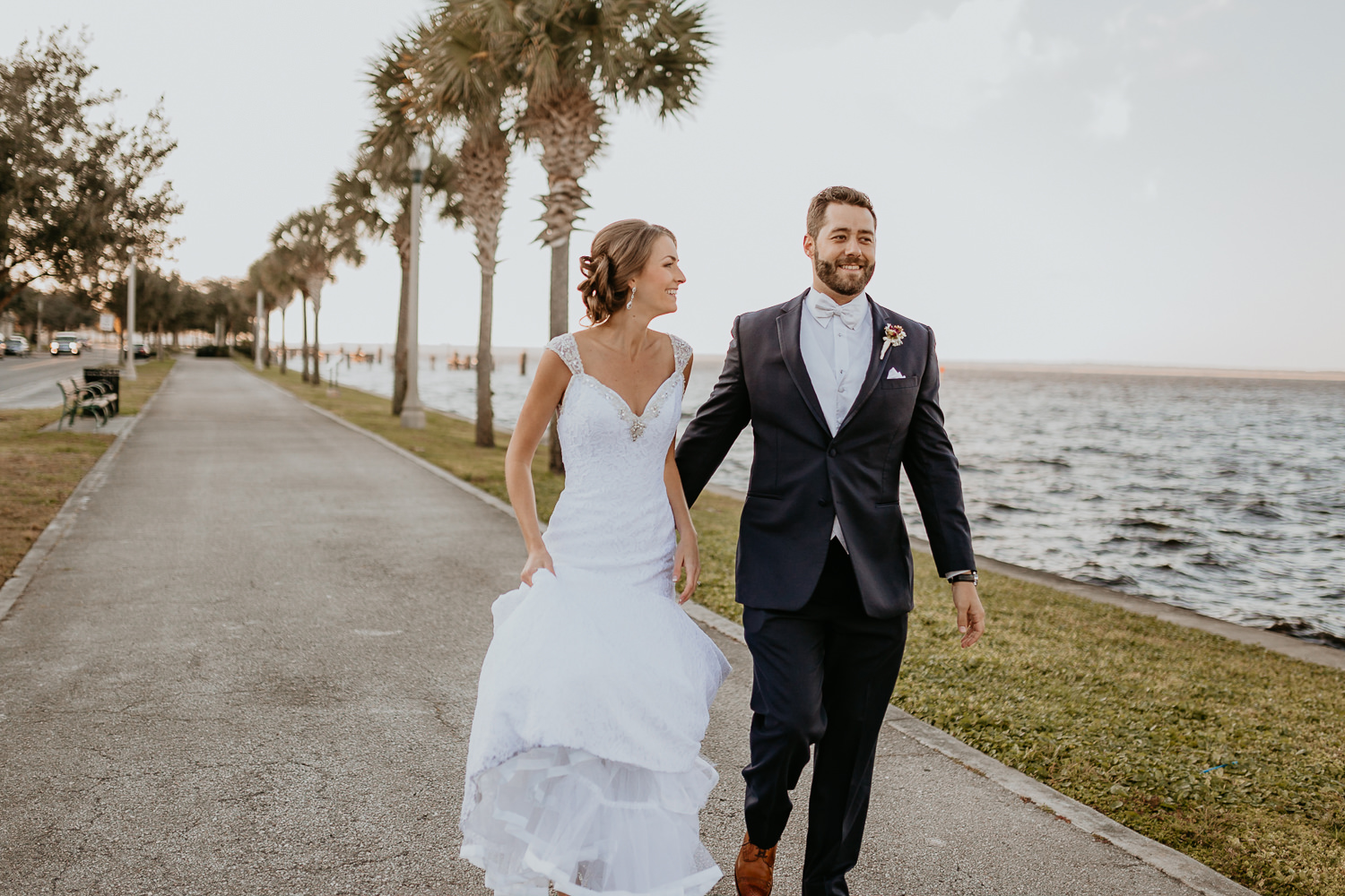 newlyweds walking together down street next to lake lined with palm trees