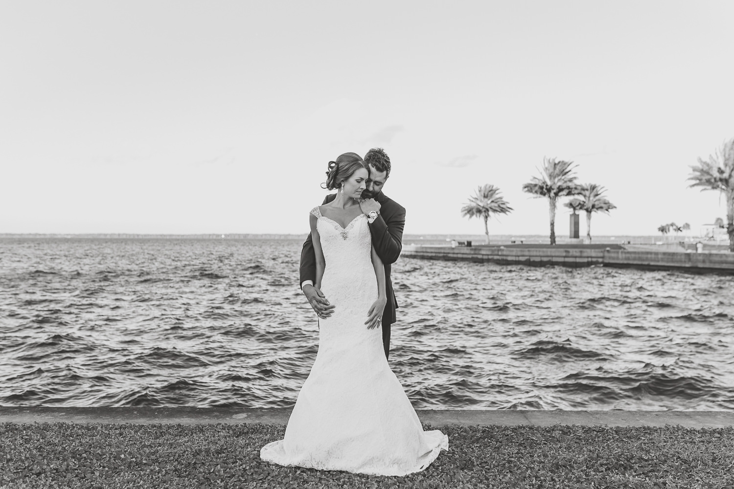 black and white of groom hugging bride from behind with Sanford lake in background