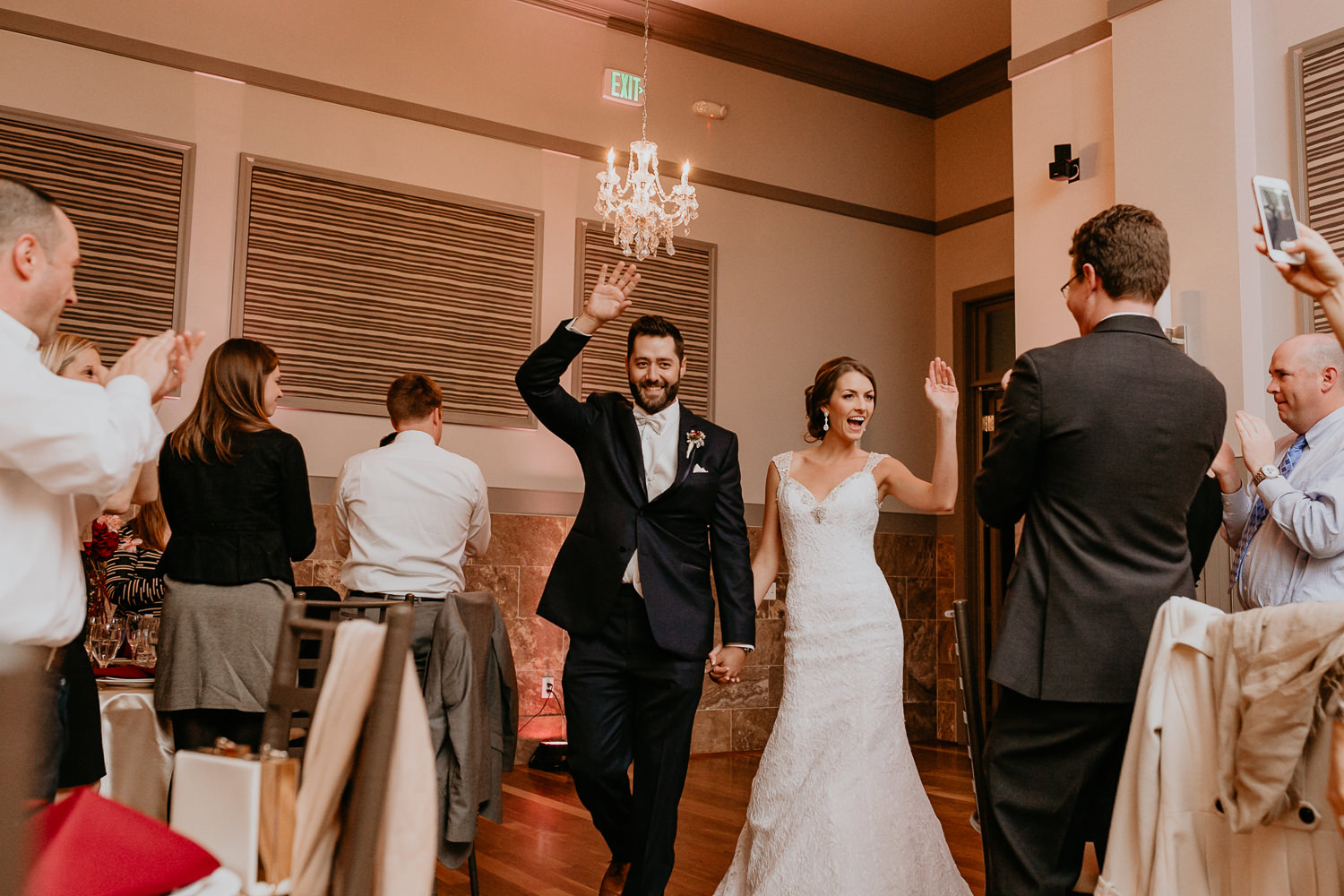 newlyweds entering their reception hands in the air